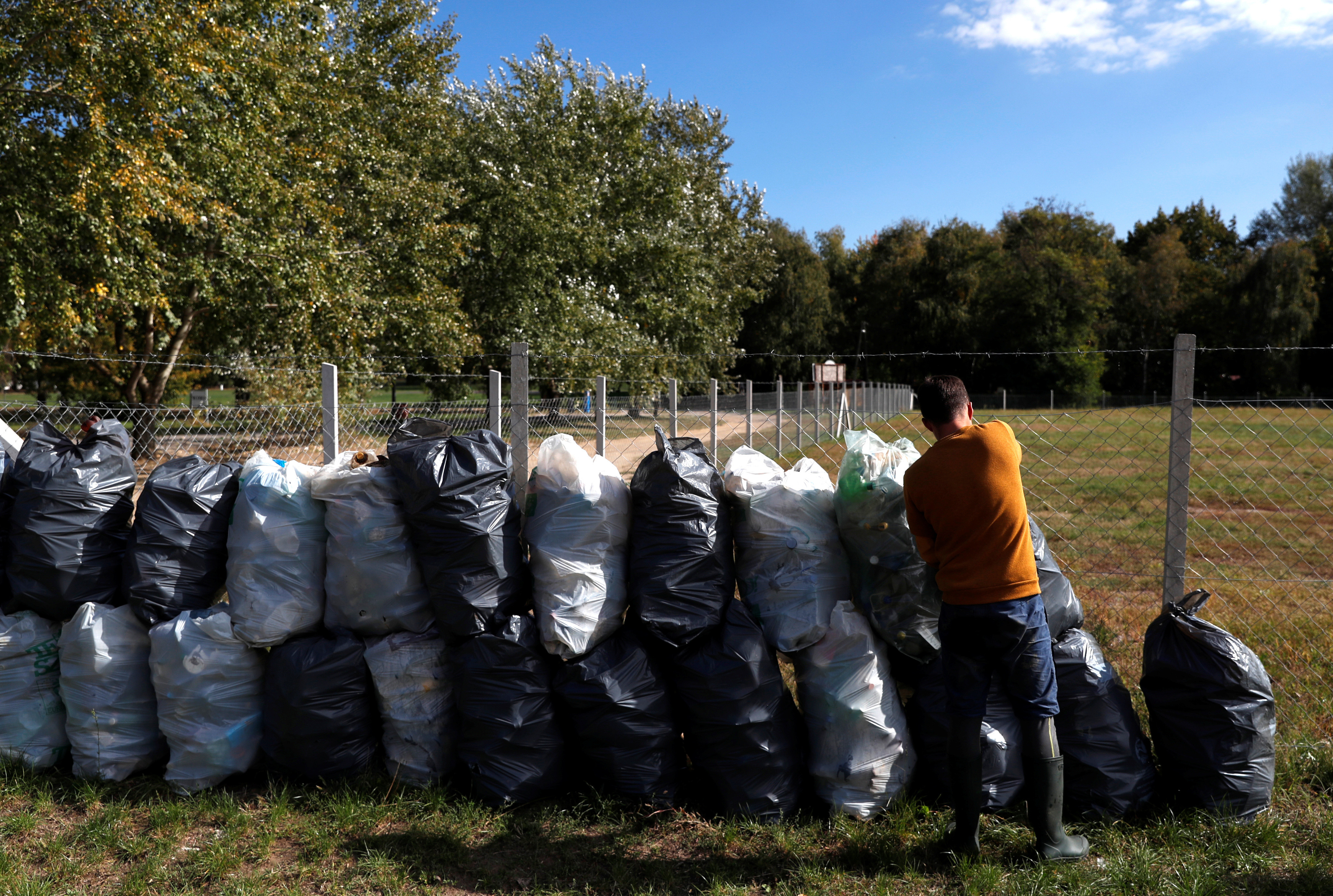 Bence Pardy, 32-year-old, takes plastic bags full of waste in Tiszafured, Hungary, October 1, 2019. Picture taken October 1, 2019. REUTERS/Bernadett Szabo - RC1146297110