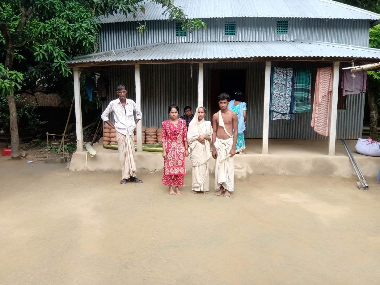 A view of the widow of Mongol Chandra Sarker (in white sari) with her daughter and son in front of the family's tin house in central Bangladesh's Ghior sub-district, September 1, 2019.