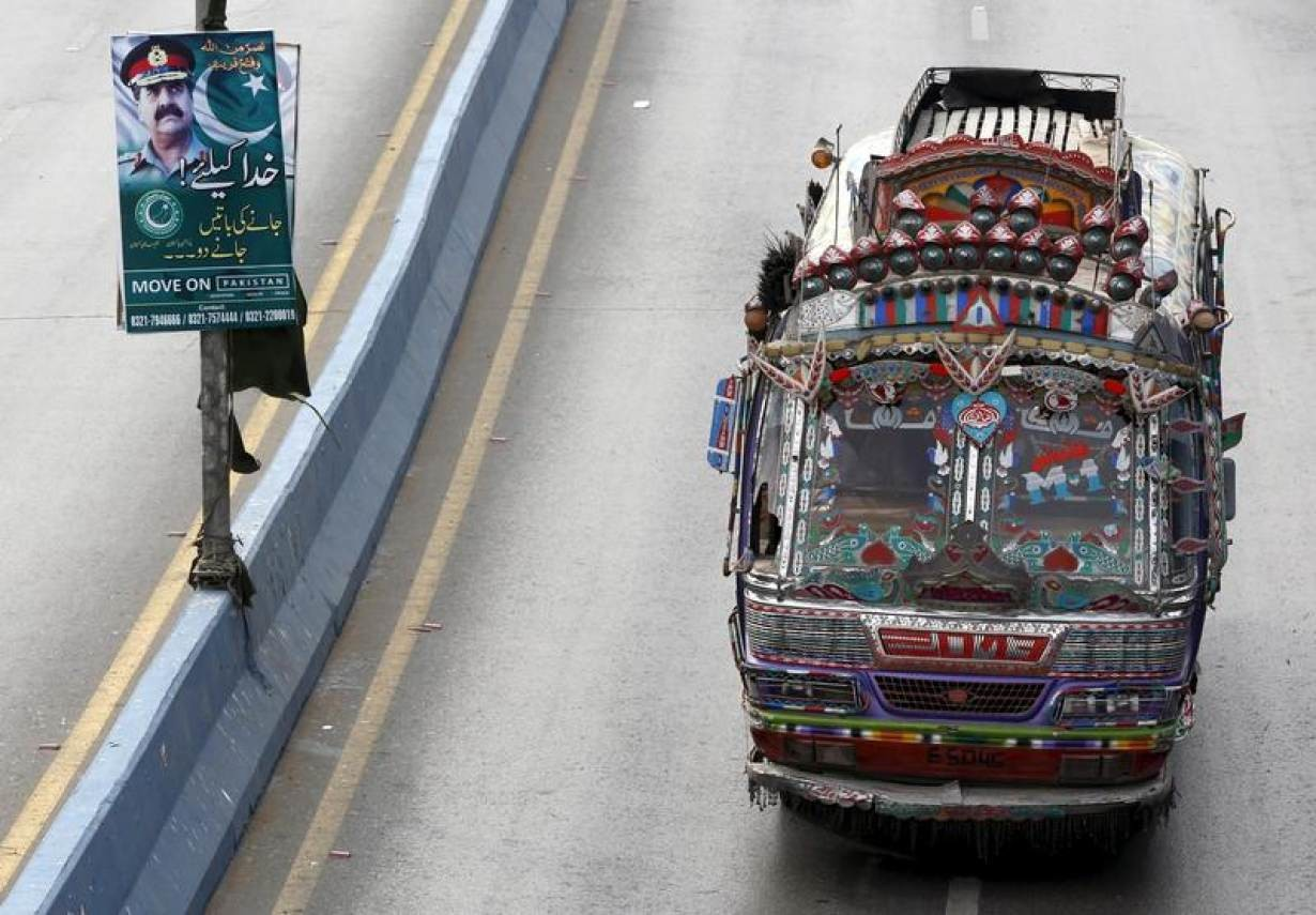 A bus moves past a banner hanging on a light pole with the picture of Pakistan's Army Chief of Staff General Raheel Sharif along a road in Karachi, February 25, 2016.