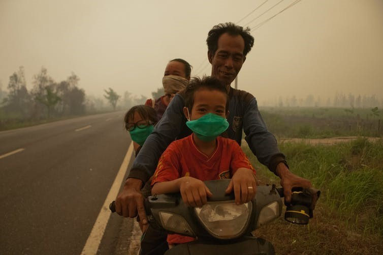 A family rides through thick haze in Kalimantan, 2015.