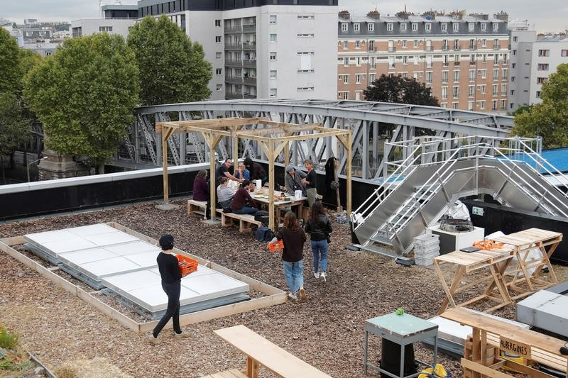 Poste office employees eat a lunch with products from a 900 square meters farm garden on the rooftop of their postal sorting center, as part of a project by Facteur Graine association to transform a city rooftop as a vegetable garden to grow fruits, vegetables, aromatic and medicinal plants, with also chickens and bees in Paris, France, September 22, 2017. Picture taken September 22, 2017.  REUTERS/Charles Platiau - RC14D74AD130