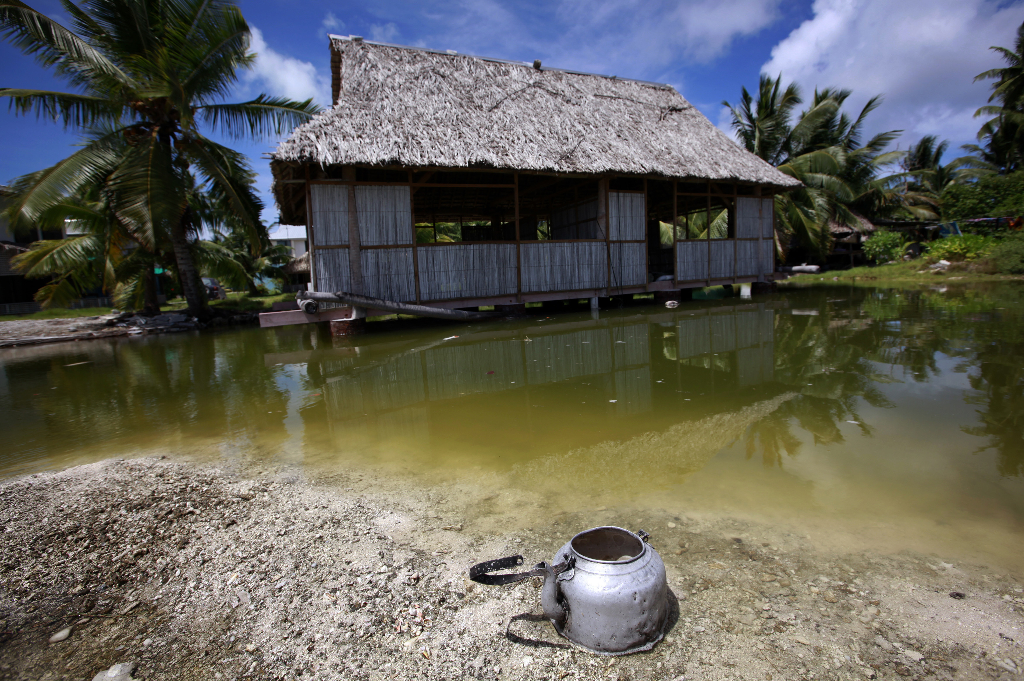 An abandoned house that is affected by seawater during high-tides stands next to a small lagoon near the village of Tangintebu on South Tarawa in the central Pacific island nation of Kiribati May 25, 2013. Kiribati consists of a chain of 33 atolls and islands that stand just metres above sea level, spread over a huge expanse of otherwise empty ocean. With surrounding sea levels rising, Kiribati President Anote Tong has predicted his country will likely become uninhabitable in 30-60 years because of inundation and contamination of its freshwater supplies. Picture taken May 25, 2013. REUTERS/David Gray (KIRIBATI - Tags: ENVIRONMENT POLITICS SOCIETY)ATTENTION EDITORS: PICTURE 09 OF 42 FOR PACKAGE 'KIRIBATI - GONE IN 60 YEARS'. SEARCH 'KIRIBATI' FOR ALL IMAGES - RTX10LQV