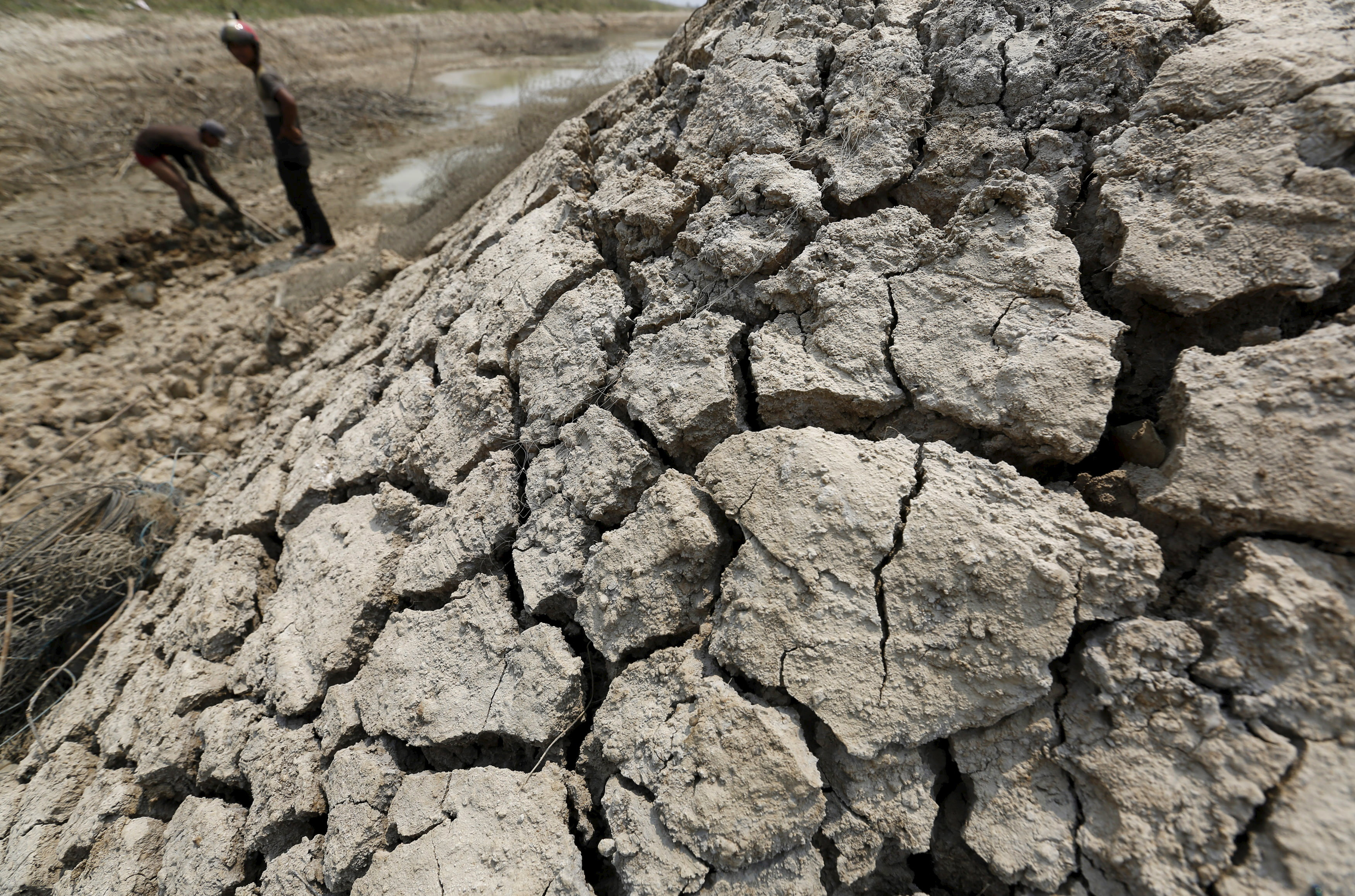 A man works at a dried up pond at the drought-hit Kandal province, Cambodia, April 26, 2016.