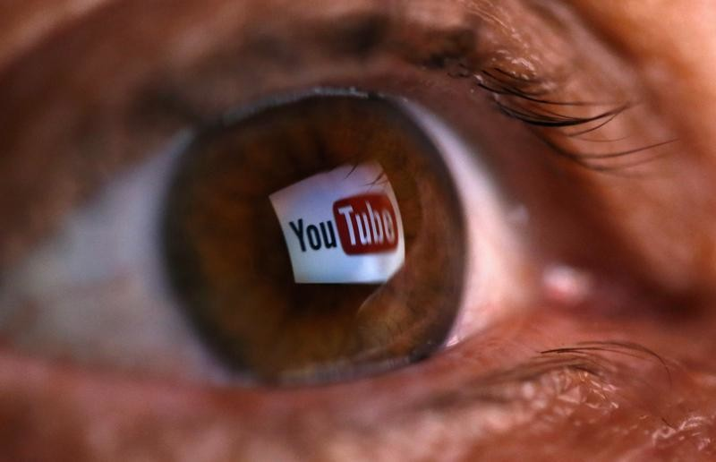 A picture illustration shows a YouTube logo reflected in a person's eye, in central Bosnian town of Zenica, early June 18, 2014. Google Inc's YouTube said on June 17, 2014 that it plans to launch a paid streaming music service, amid criticism that its existing, free video website might block the music videos of labels that do not agree to its terms. YouTube has partnered with