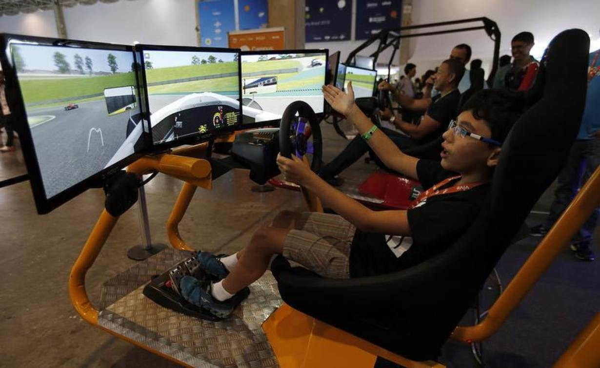 Participants play in a Formula One car simulator during the Campus Party event in Sao Paulo February 4, 2015.