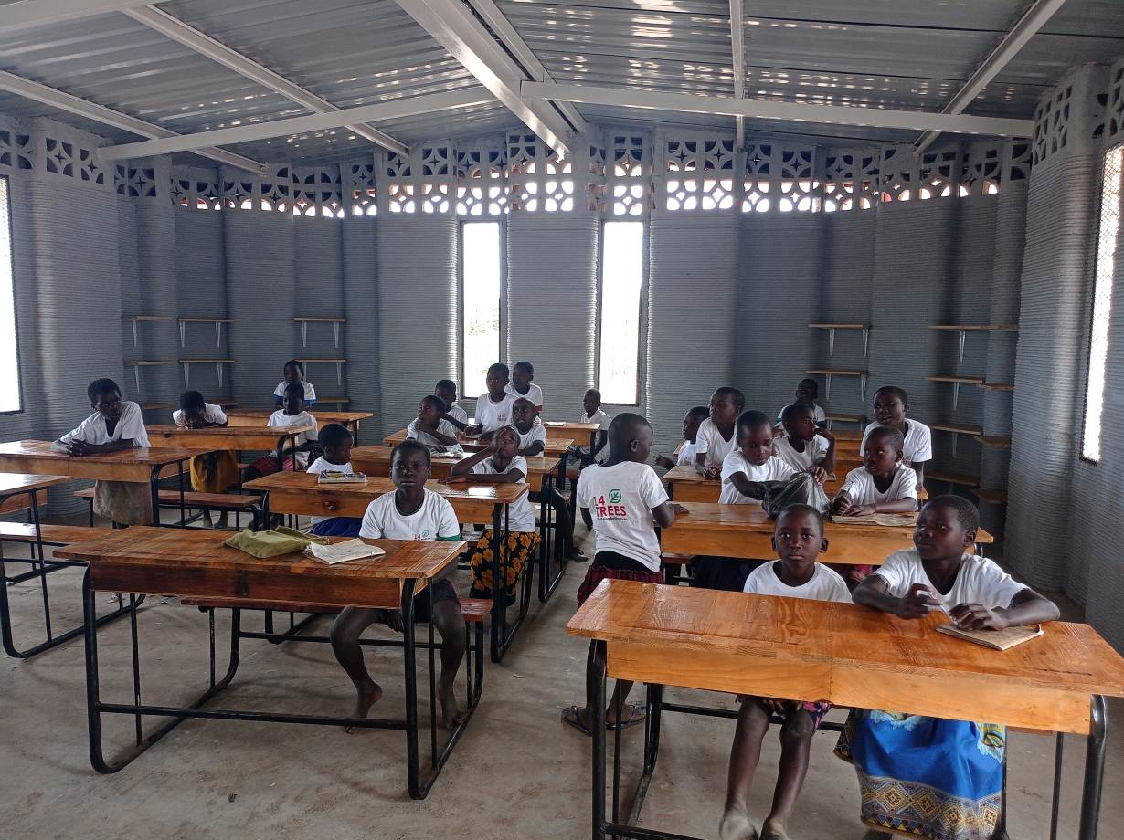 these students are sitting inside their new 3D printed school, built to accommodate up to 50 students, in Salima, Malawi