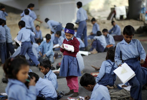 A schoolgirl reads from a textbook at an open-air school in New Delhi November 20, 2014. Picture taken November 20. To match story INDIA-RELIGION/EDUCATION       REUTERS/Anindito Mukherjee  (INDIA - Tags: POLITICS EDUCATION RELIGION) - GM1EABL12DD01
