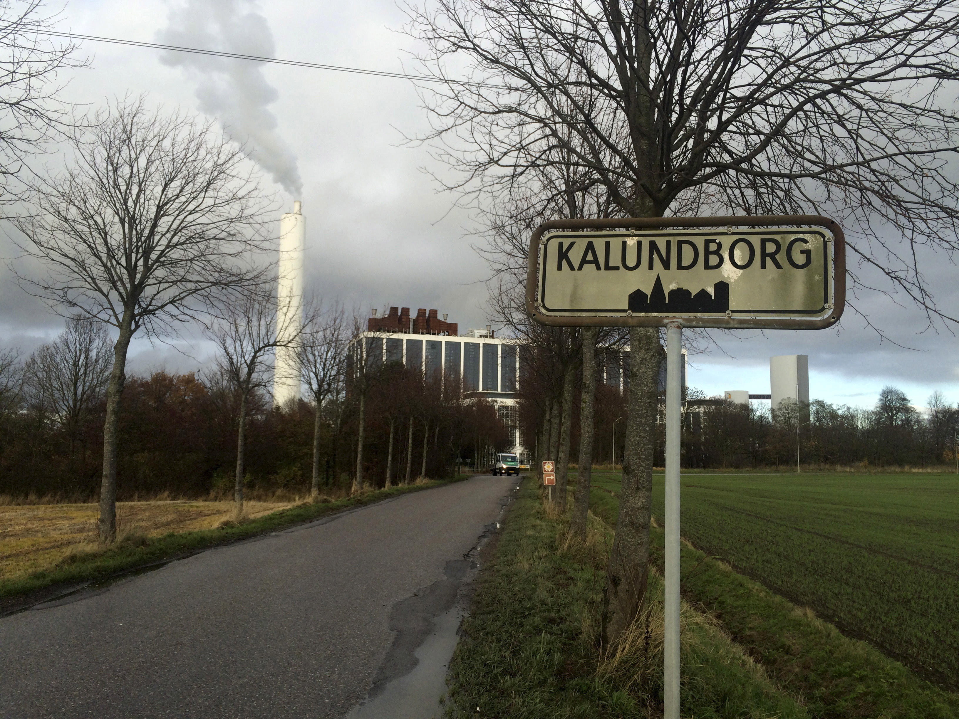 A car drives in front of DONG Energy's power station, which provides steam, ash and gypsum as waste products to other companies for their use in Kalundborg, Denmark, November 20, 2015. As pioneers of so-called industrial symbiosis, these companies swap waste and byproducts to cut costs and carbon dioxide (CO2) emissions profitably -- an approach that offers big business a financial incentive that could be crucial to nations striving to meet targets agreed at this month's global climate summit. Their success has attracted attention globally, with more than 30 corporate and municipal delegations from 20 countries visiting the town this year, including mayors from China's fast-growing Guandong province. To match story INDUSTRY-EMISSIONS/    REUTERS/Sabina Zawadzki - RTX1ZA4G