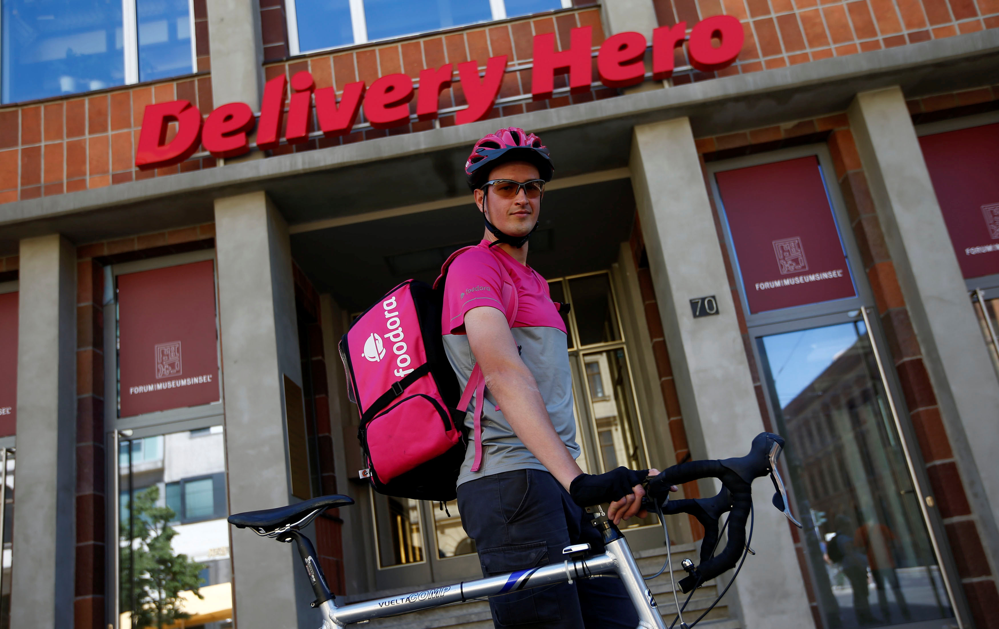 A Foodora cyclist in front of Delivery Hero headquarters in Berlin