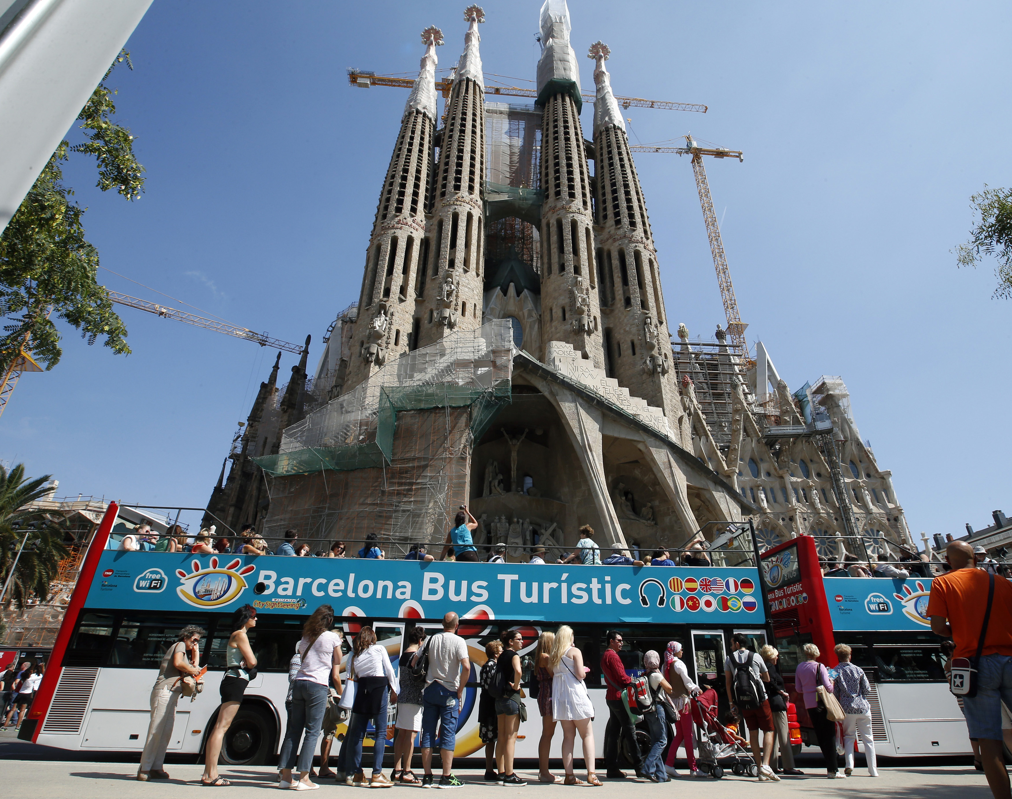 People queue up at a city tour bus stop in front of the Basilica Sagrada Familia in Barcelona, September 13, 2013. Sunseekers spurning unrest in Egypt and Turkey flocked to Spain in record numbers in August, setting the country up for its best-ever year for visitors and giving a boost to the ailing economy. Tourism contributed over 5 percent of Spain's economy or GDP in 2012 and provided around 900,000 jobs, according to Euromonitor, in a country where one in four is out of work, meaning a boost to tourist figures should be good news as other sectors flag. Picture taken September 13, 2013.  REUTERS/Albert Gea (SPAIN - Tags: TRAVEL BUSINESS) - RTX13WQ6