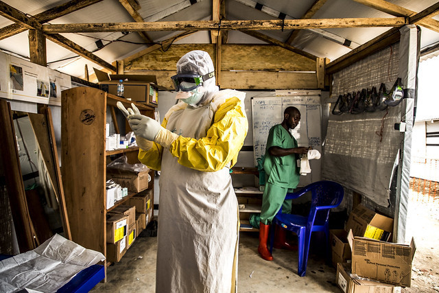 17 January 2019 - Beni, North Kivu region, Democratic Republic of Congo. Doctor Junior Ikomo puts the Personal Protective Equipment on, inlduing gloves, before going to treat patients who are suspected of being infected by Ebola.
