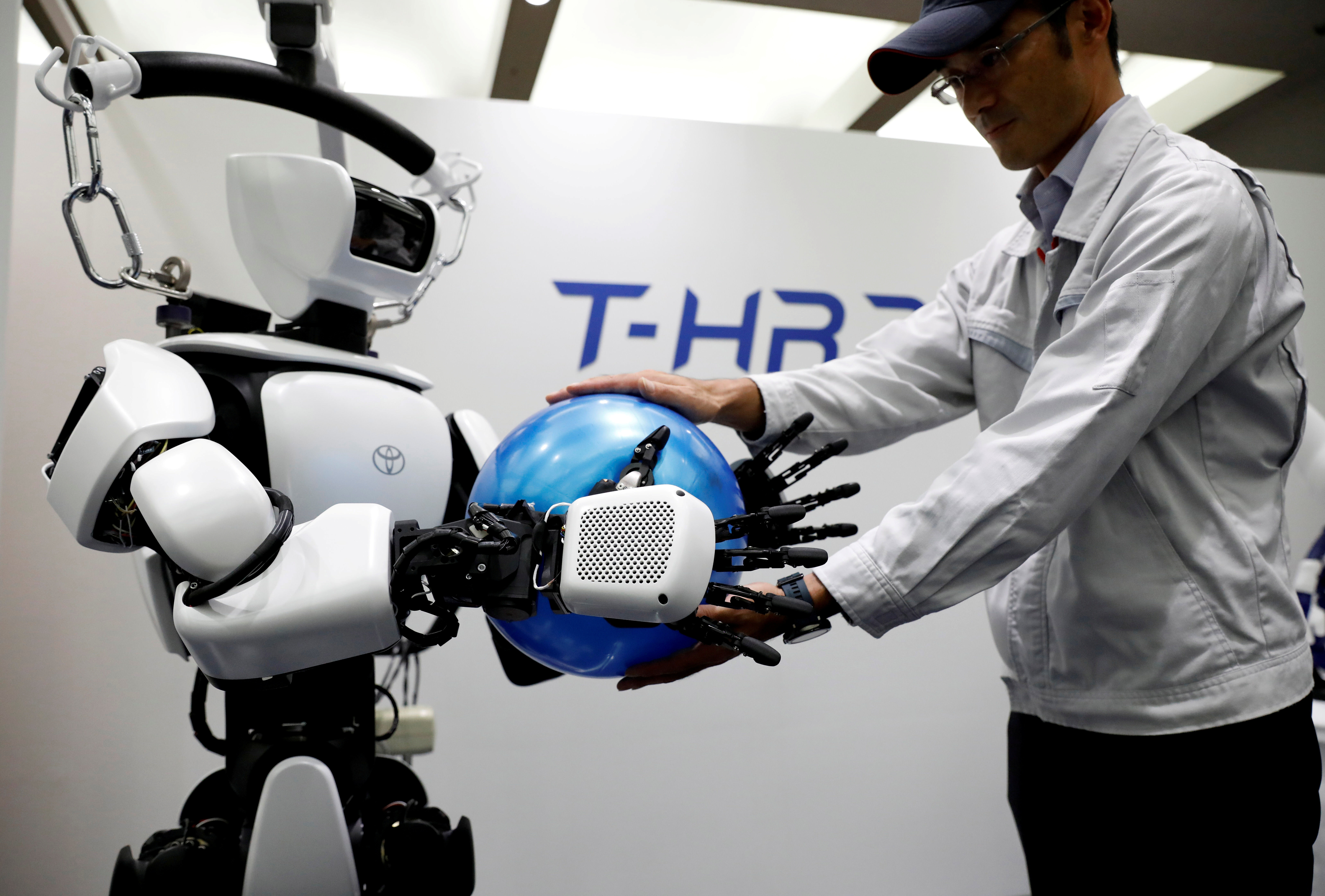 An employee of Toyota Motor Corp. demonstrates T-HR3 humanoid robot which will be used to support the Tokyo 2020 Olympic and Paralympic Games, during a press preview in Tokyo, Japan July 18, 2019. Picture taken July 18, 2019.  REUTERS/Issei Kato - RC1546F907F0