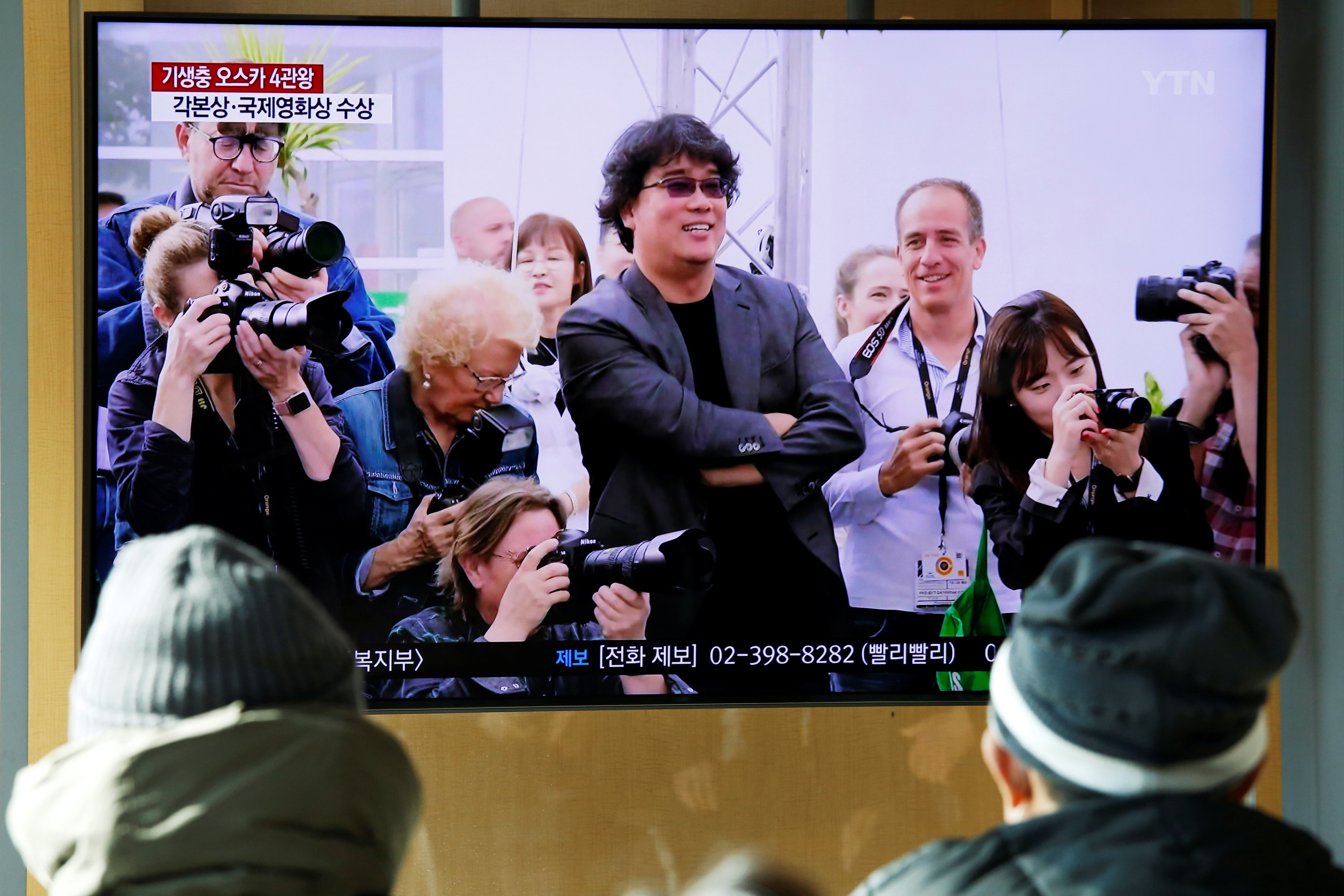 People watch a TV broadcasting a news report onSouth Korean directorBongJoon-ho whowonfourOscarswith his film