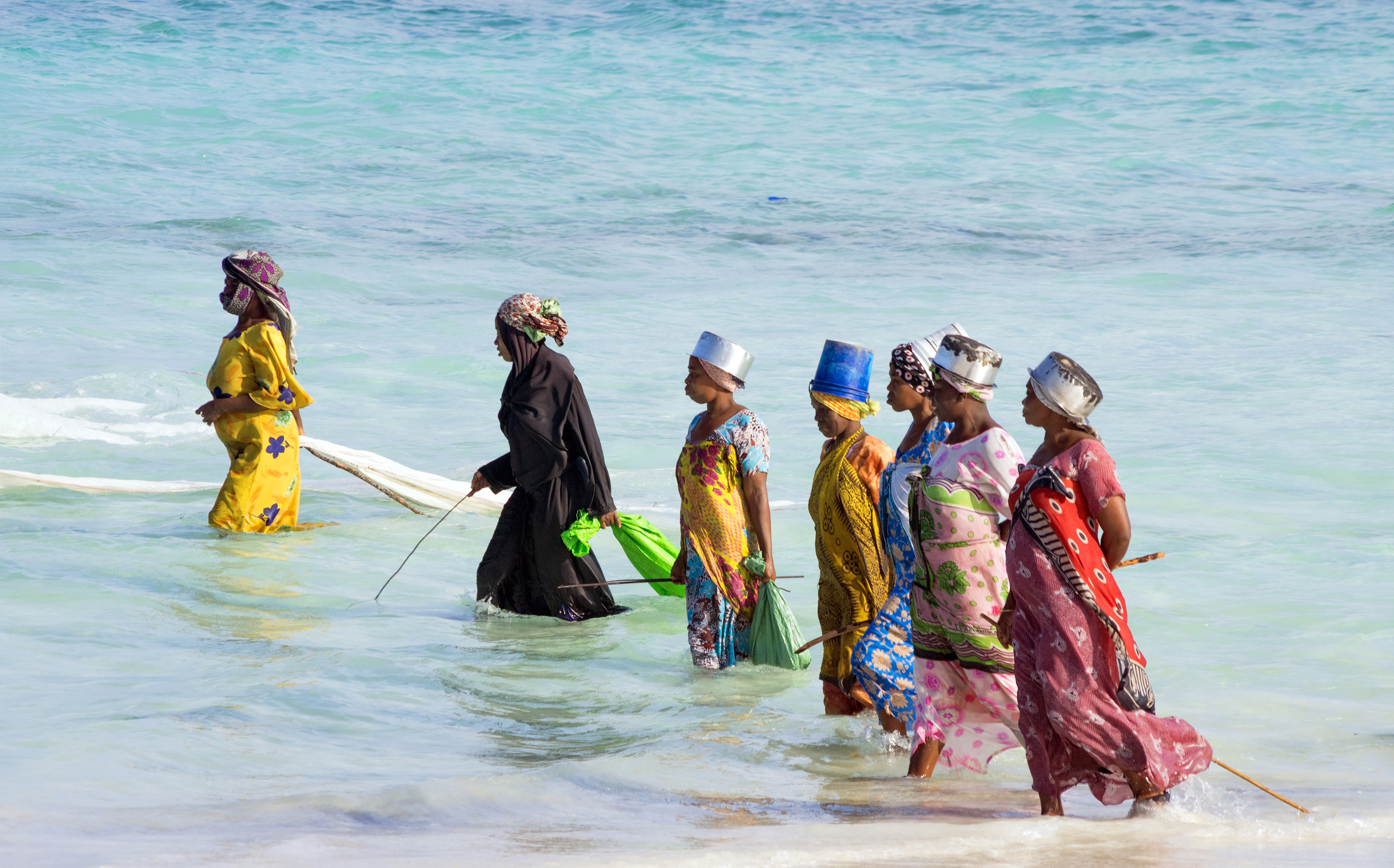 Zanzibar, Tanzania. Women from a fishing village are catching small fish off the coast of the ocean.