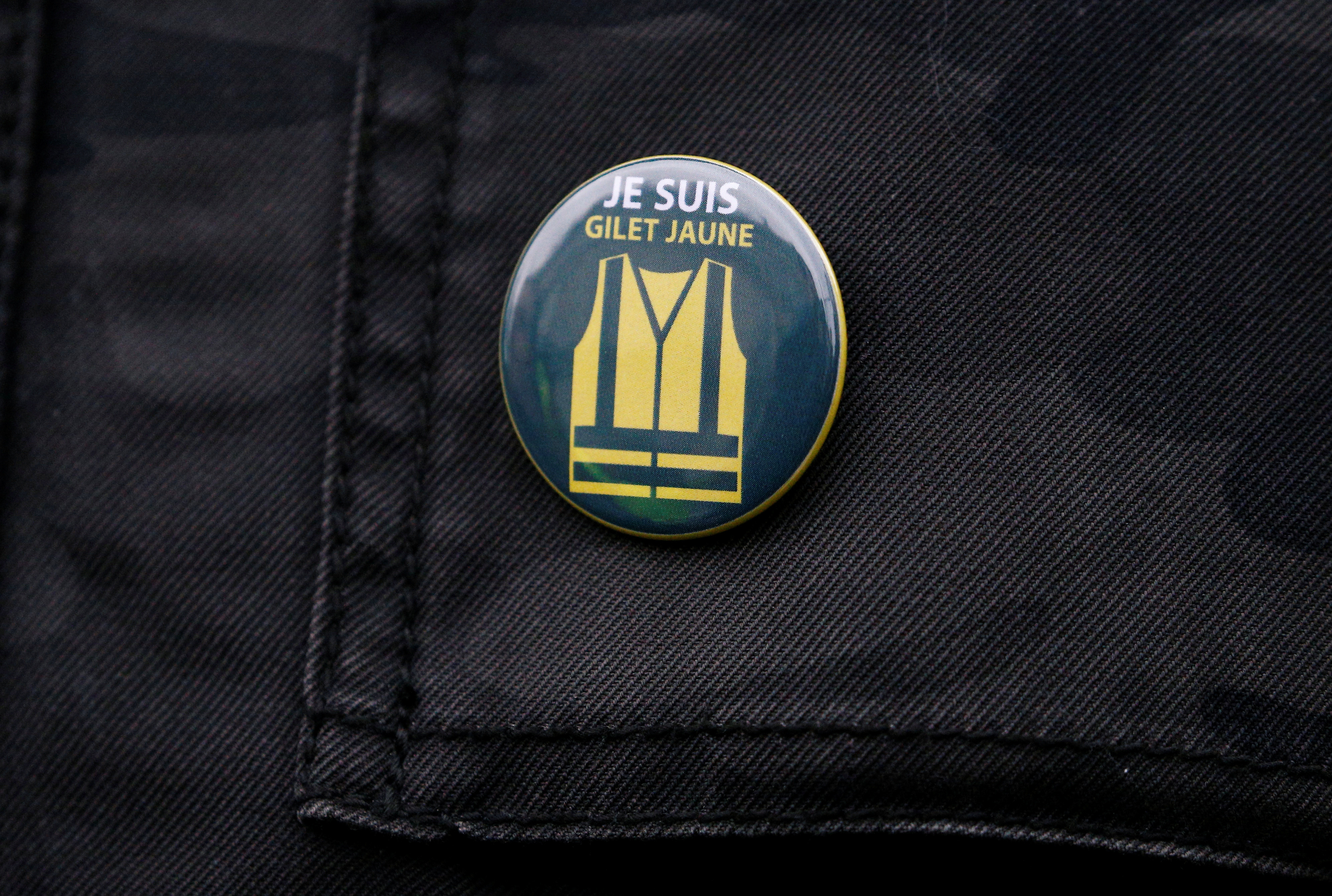 A protester wears a vest pin on which is read: