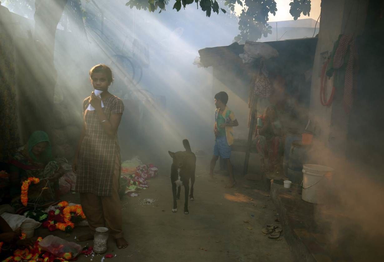 A girl stands outside her house after a health worker fumigates a residential area to prevent the spread of mosquito-borne diseases in Ahmedabad, India, October 26, 2018.