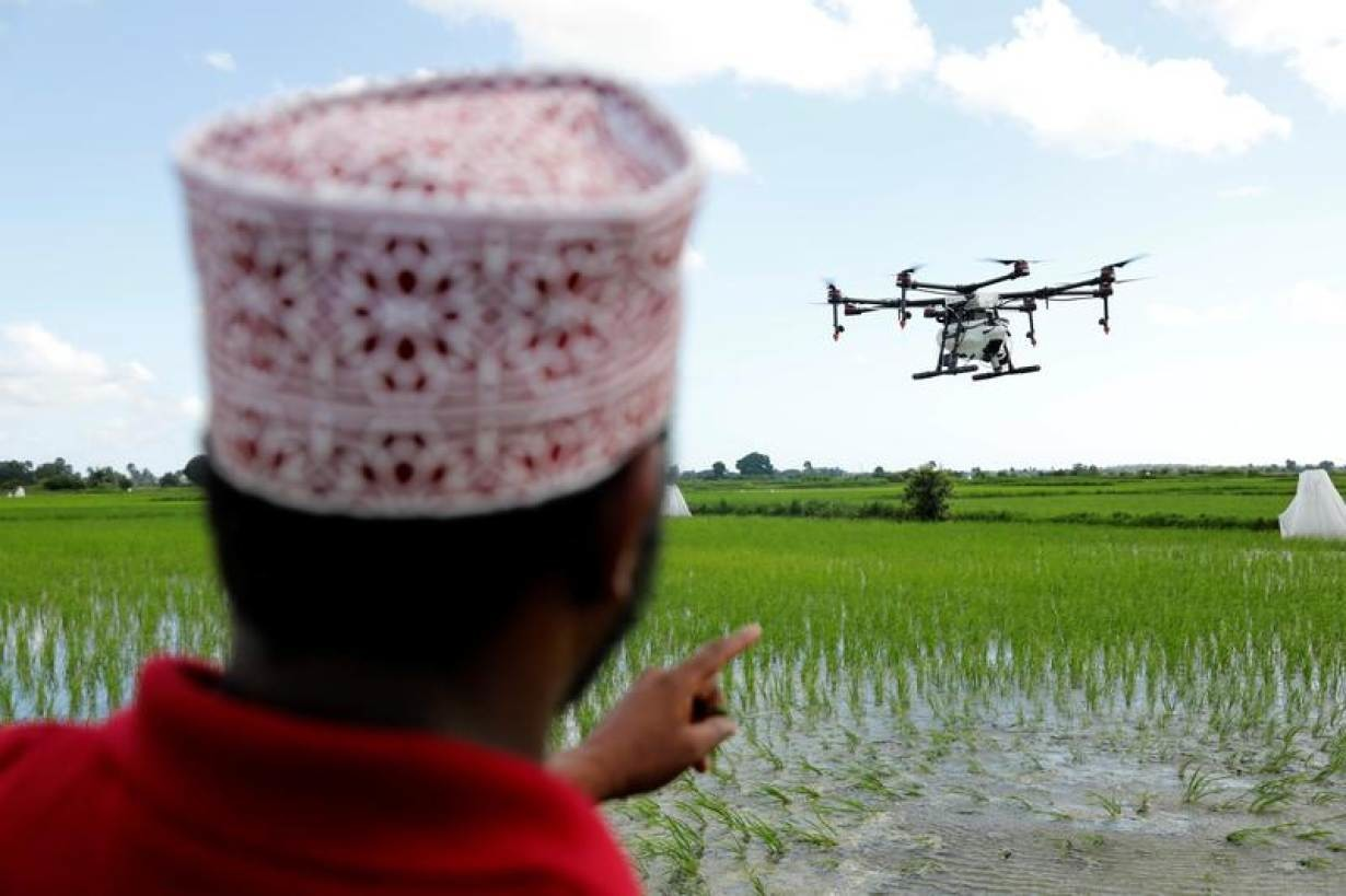 A drone pilot watches a customized drone fly over a rice field during a test using drone technology in the fight against malaria, near Zanzibar City, Zanzibar, October 31, 2019.