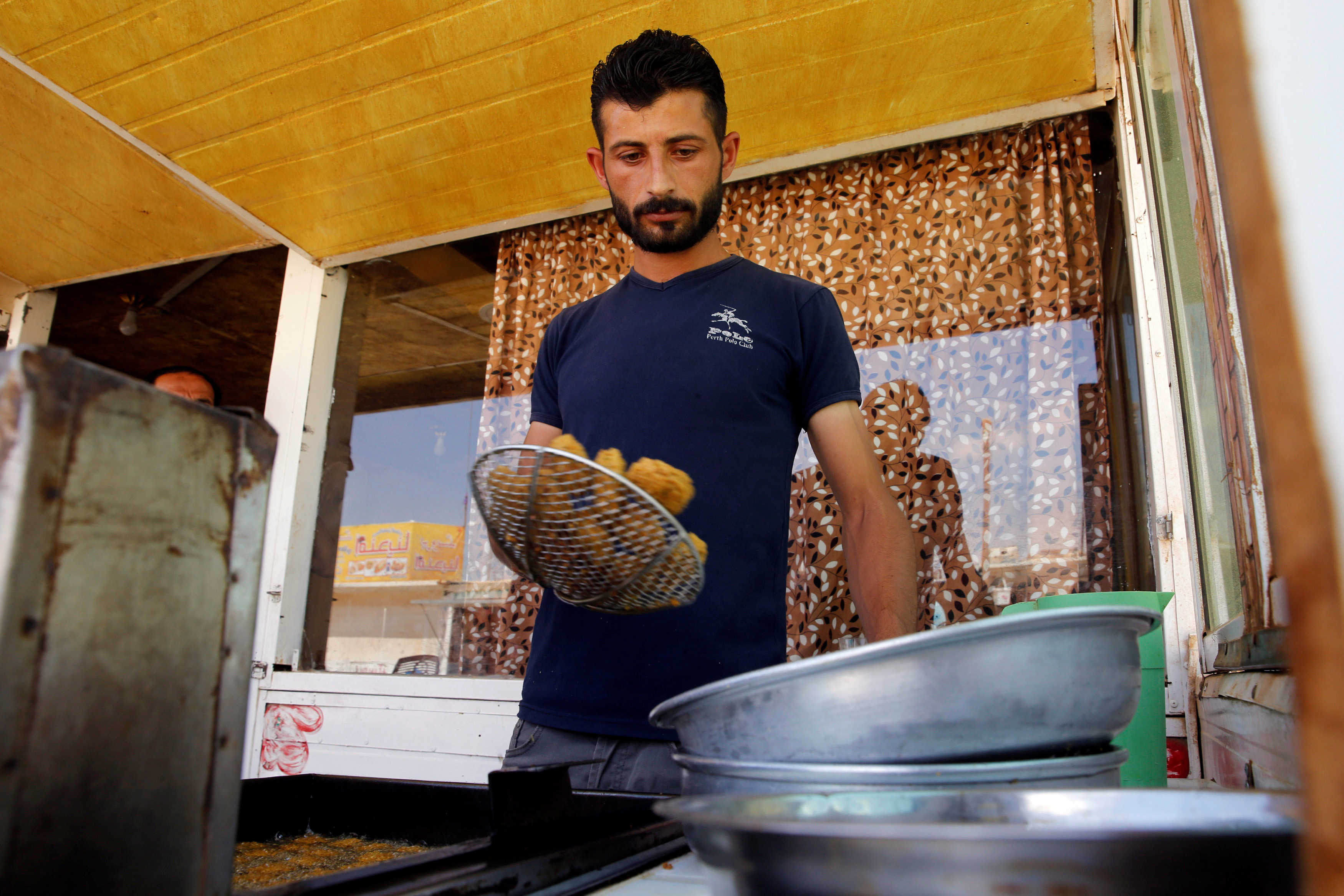A Syrian refugee works at his restaurant in the Zaatari camp.