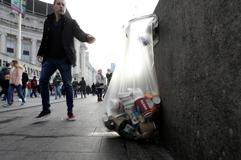 A pedestrian throws a discarded item into a bag containing paper cups alongside other rubbish on the Southbank, in London, Britain January 6, 2018. REUTERS/Simon Dawson - RC1B0A3222C0