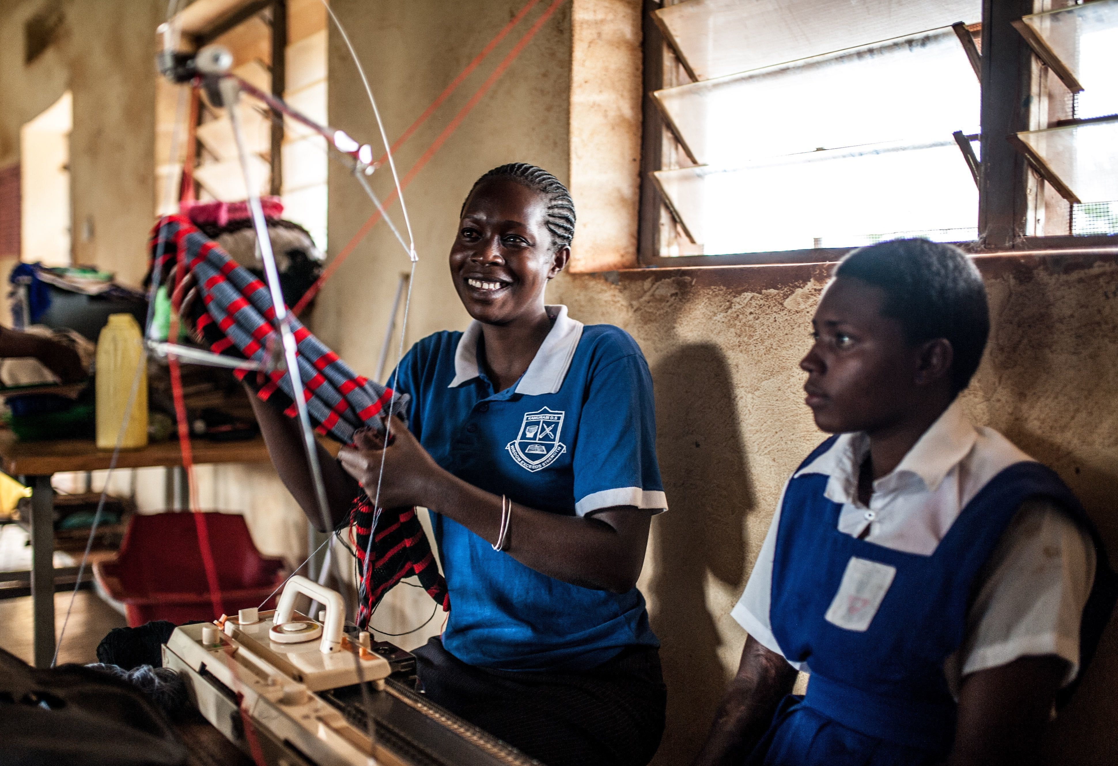 Sylvia Kalibeera with her hearing impaired student Rachel Akuguzibwe, during a knitting class at Kamurasi Demonstration School, Masindi.