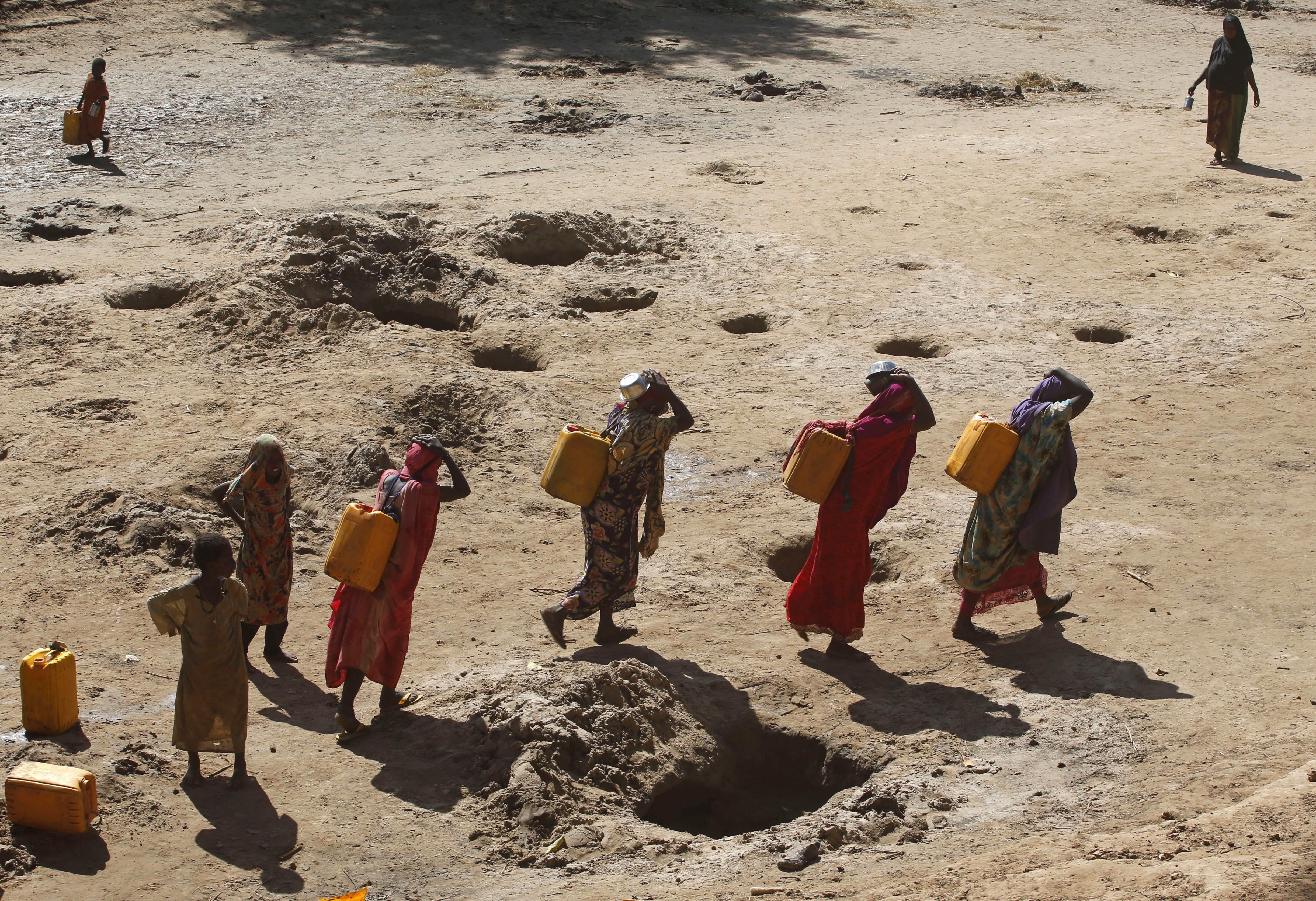 On women's shoulders … women carry jerry cans of water from shallow wells dug in the Shabelle River bed in Somalia, which is dry due to drought.