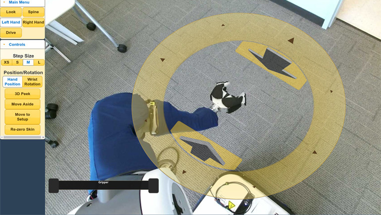 T his view through the PR2's cameras shows the environment around the robot. Clicking the yellow disc allows users the control the arm.