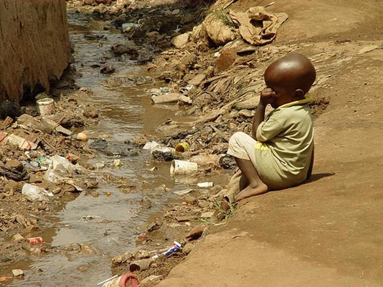 Child in slum in Kampala, Uganda, next to open sewage. Poor health conditions may lead to severe stunting in children. July 2007.I.