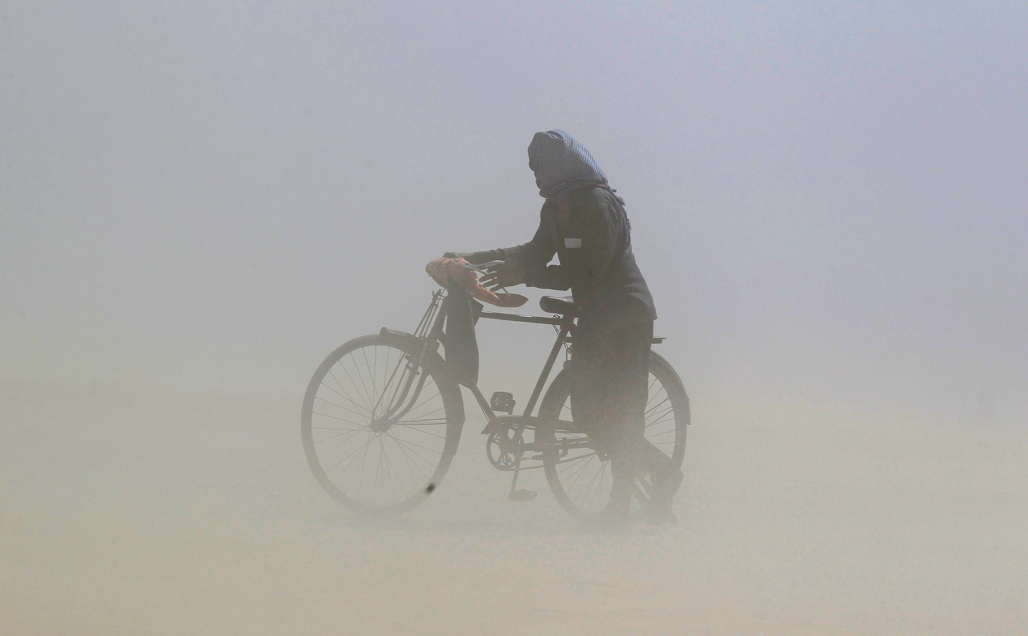 A man covers his face as he pushes a bicycle through a dust storm on the banks of the Ganga river in Allahabad, India