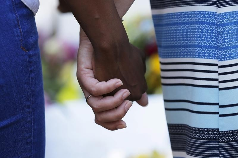 Mourners hold hands outside the Emanuel African Methodist Episcopal Church in Charleston, South Carolina, June 18, 2015 a day after a mass shooting left nine dead during a bible study at the church. Dylann Roof, a 21-year-old white man, was arrested on Thursday on suspicion of having fatally shot nine people at the historic African-American church in South Carolina. The U.S. Department of Justice is investigating Wednesday's attack as a hate crime, motivated by racism or other prejudice.
