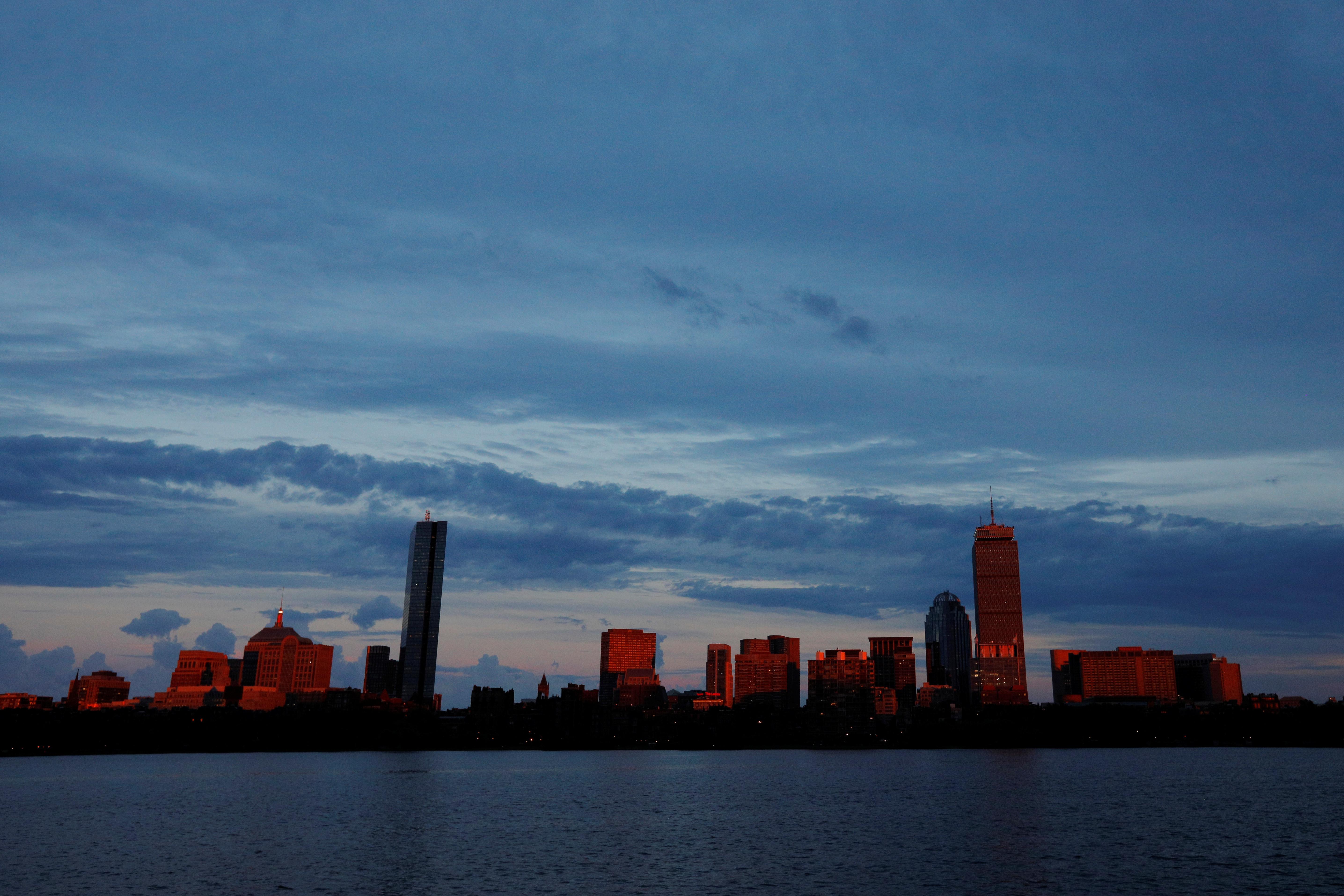 The setting sun reflects off the Boston skyline across the Charles River in Cambridge, Massachusetts, U.S., June 27, 2017.