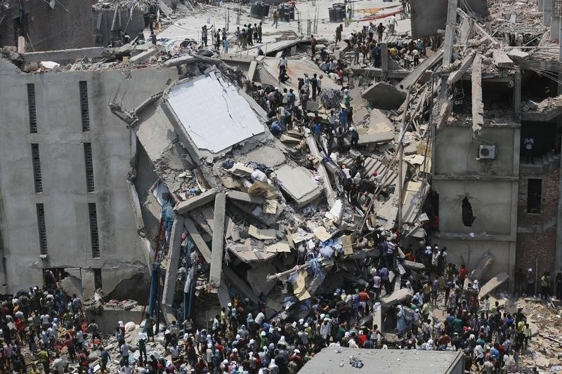 People rescue garment workers trapped under rubble at the Rana Plaza building after it collapsed, in Savar, 30 km (19 miles) outside Dhaka April 24, 2013. An eight-storey block housing garment factories and a shopping centre collapsed on the outskirts of the Bangladeshi capital on Wednesday, killing at least 25 people and injuring more than 500, the Ntv television news channel reported. REUTERS/Andrew Biraj