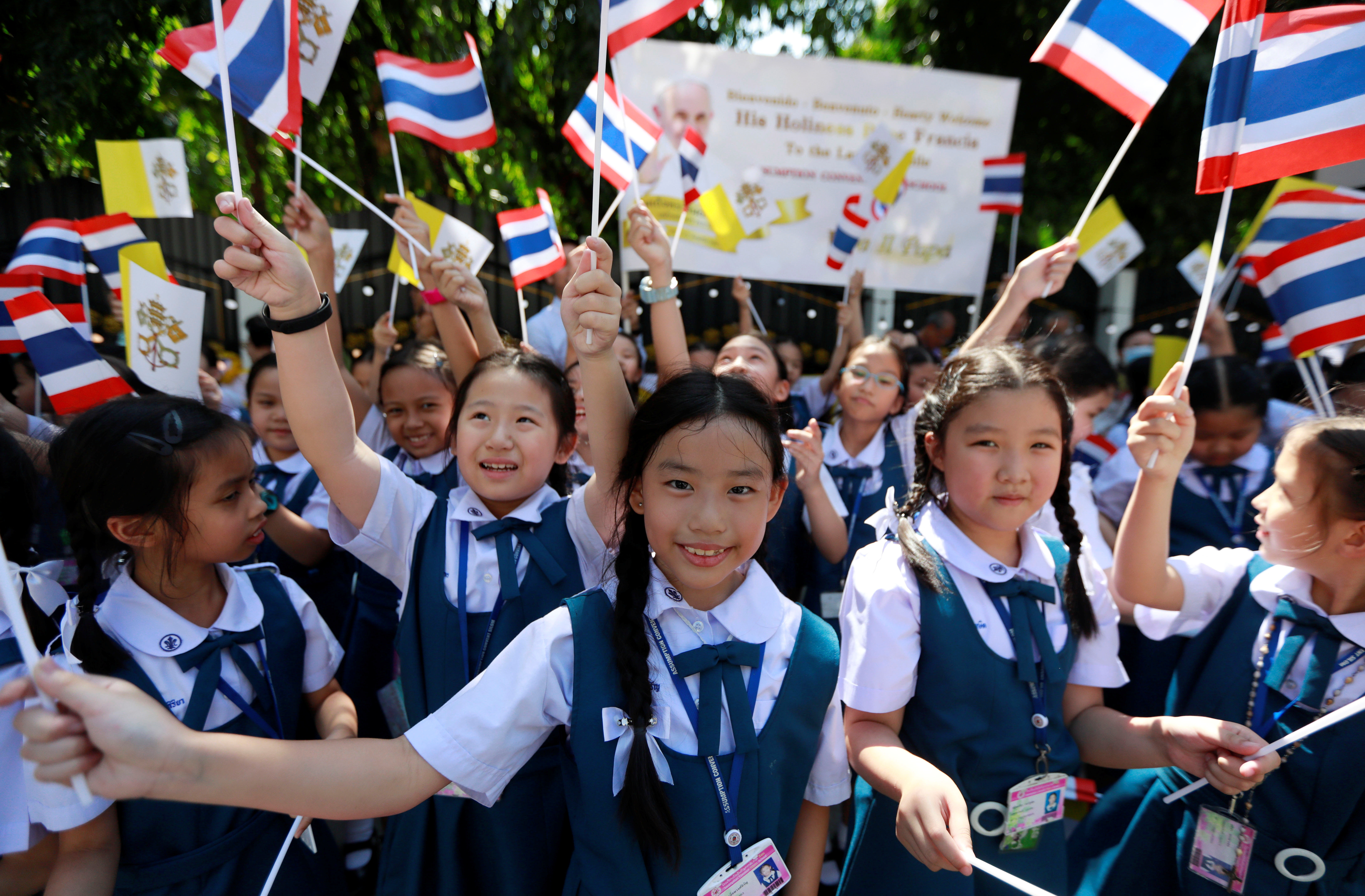 Well-wishers wave flags while waiting for the arrival of Pope Francis in Bangkok, Thailand.