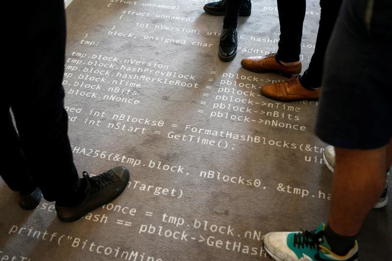 Employees of the Fintech N26 (Number26), stand on a carpet with the Bitcoin source code printed on it in Berlin, Germany, August 19, 2016.
