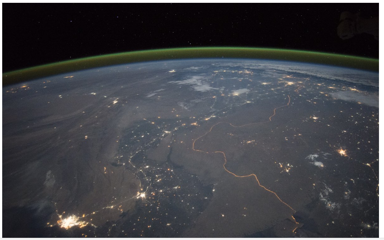 The floodlit India-Pakistan border is visible as an orange glow.
