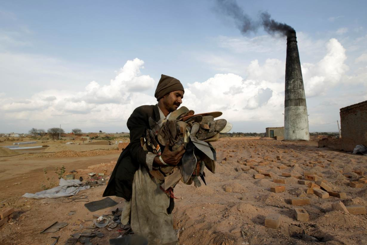 A worker carries shoes to be burned in the kiln of a brick factory in Islamabad, Pakistan March 9, 2017.