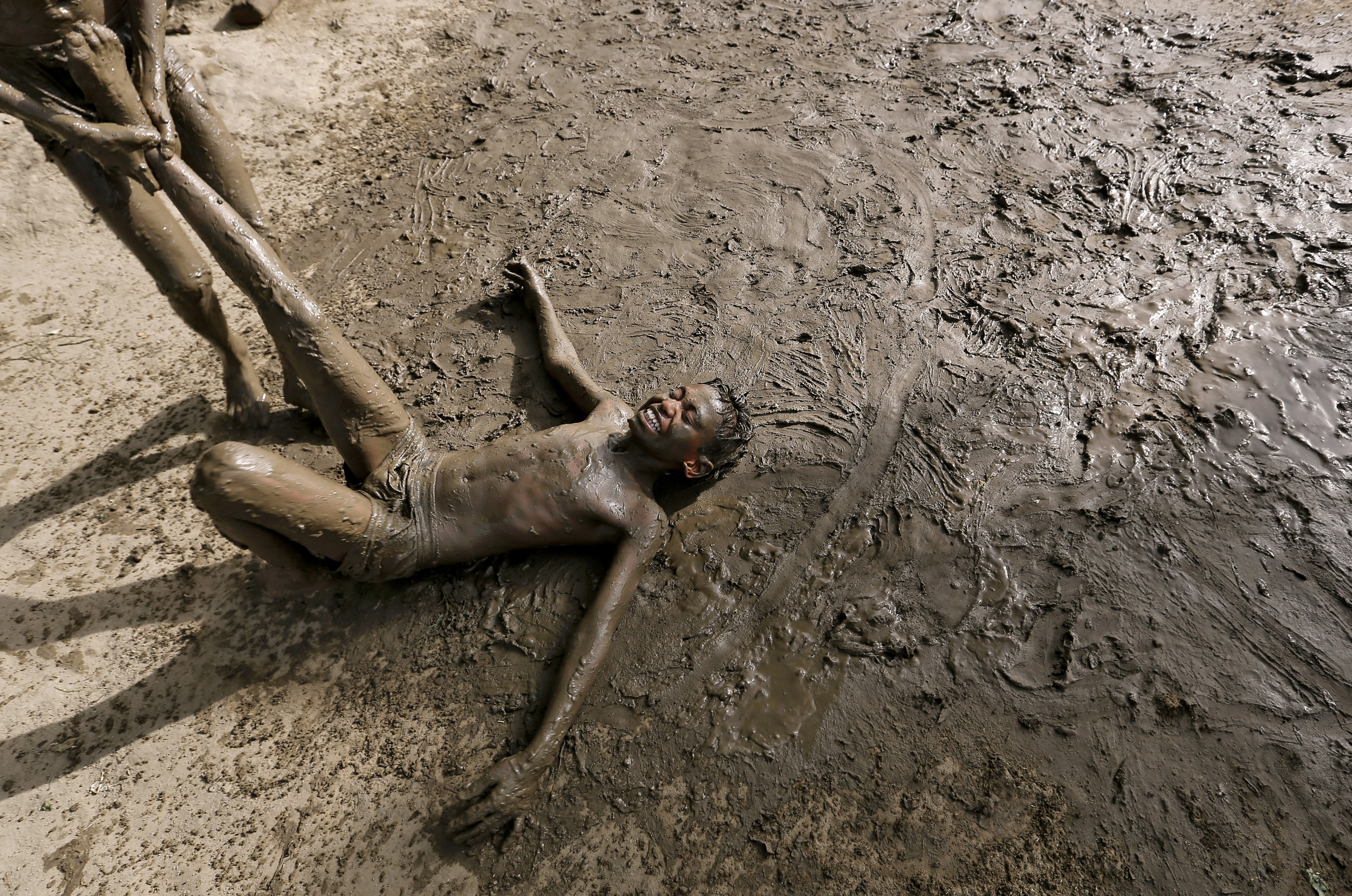 Children play in mud to cool off on a hot day in New Delhi, India