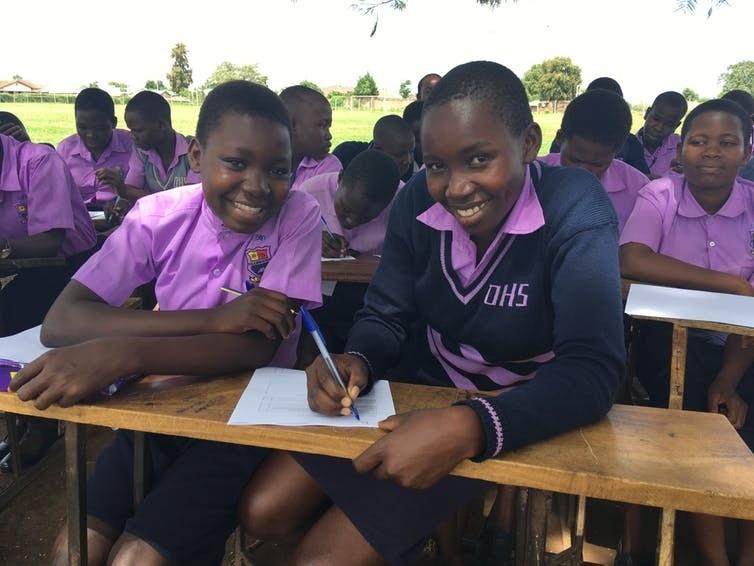 Ugandan school girls complete a feedback questionnaire.