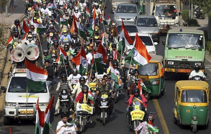 Supporters of veteran Indian social activist Anna Hazare carrying India's national flags along with the traffic take part in a rally against corruption in New Delhi December 4, 2011. Hazare, who has millions of mainly urban middle-class followers, has warned he will revive street protests that rocked the government in the summer if a bill to create a powerful corruption watchdog does not become law this year. REUTERS/Parivartan Sharma (INDIA - Tags: POLITICS CIVIL UNREST)