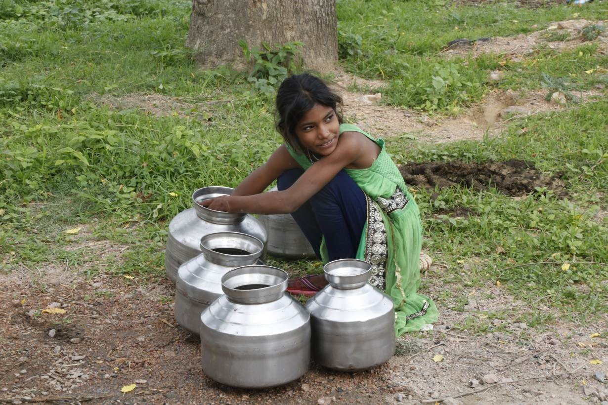 A girl cleans her metal water pots in Bundelkhand, India on July 16, 2019.