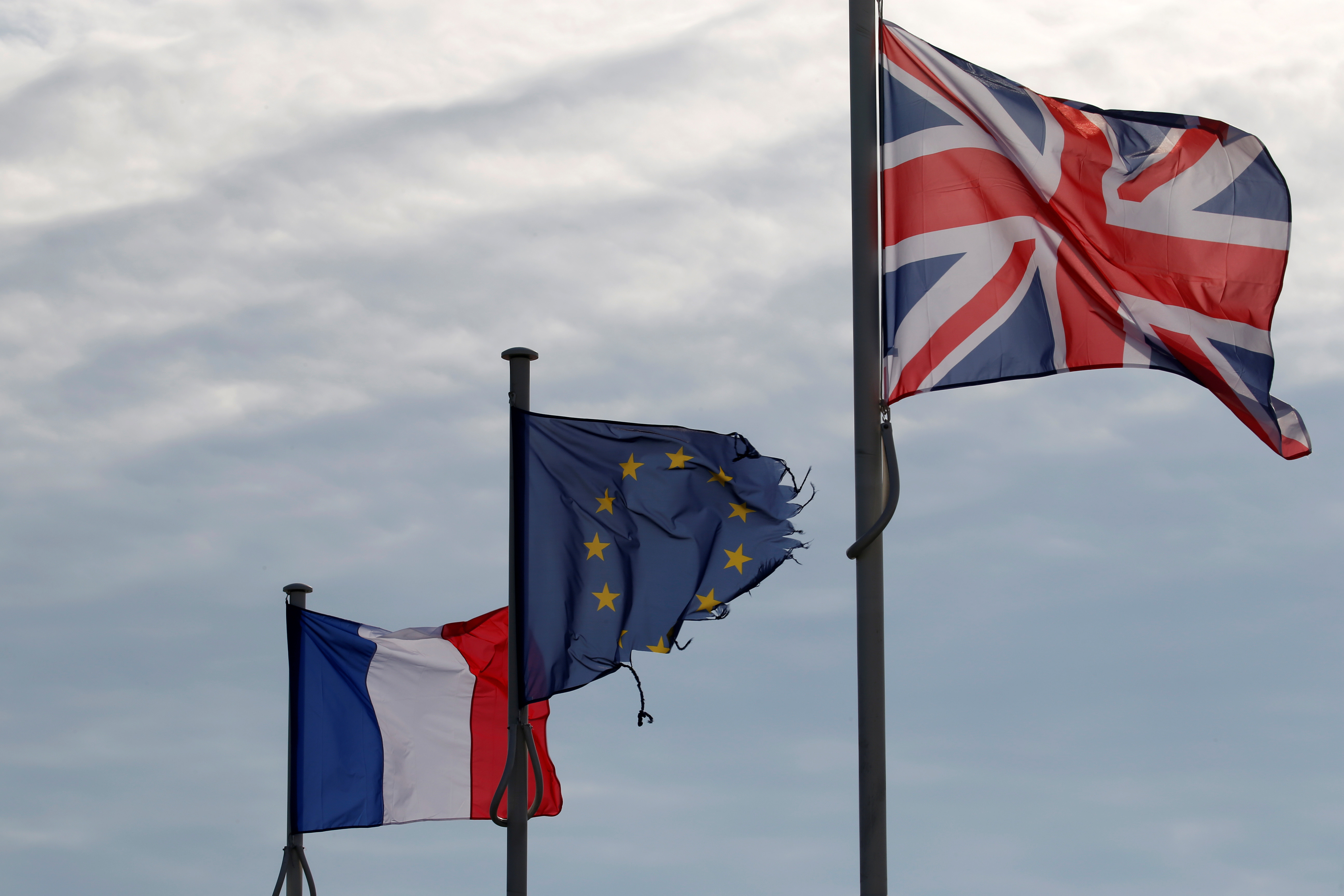 The French, British Union Jack and European flags are seen in the harbour of Calais, France, October 30, 2019. Picture taken October 30, 2019.