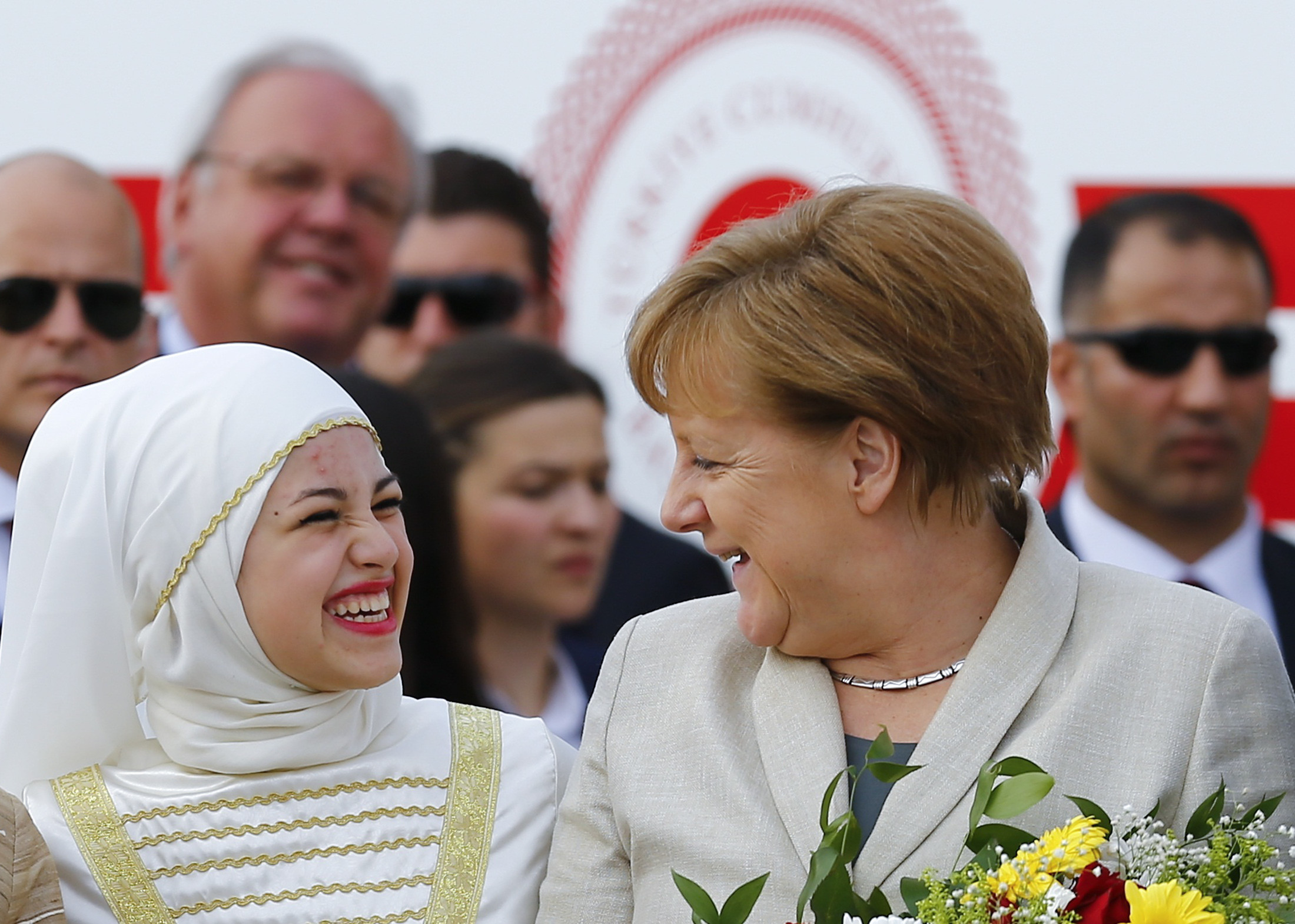 German Chancellor Angela Merkel chats with a girl during a welcoming ceremony at Nizip refugee camp near Gaziantep, Turkey, April 23, 2016. REUTERS/Umit Bektas  TPX IMAGES OF THE DAY - RTX2BCF8