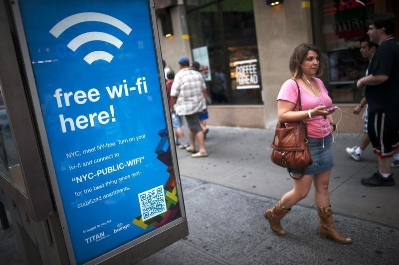 A woman walks past a WiFi-enabled phone booth in New York July 12, 2012. The New York City Department of Information Technology and Telecommunications have announced that they have converted 10 public pay phones into free WiFi hot spots as part of a pilot program to determine if it is possible to expand all city pay phones into a city-wide WiFi network.