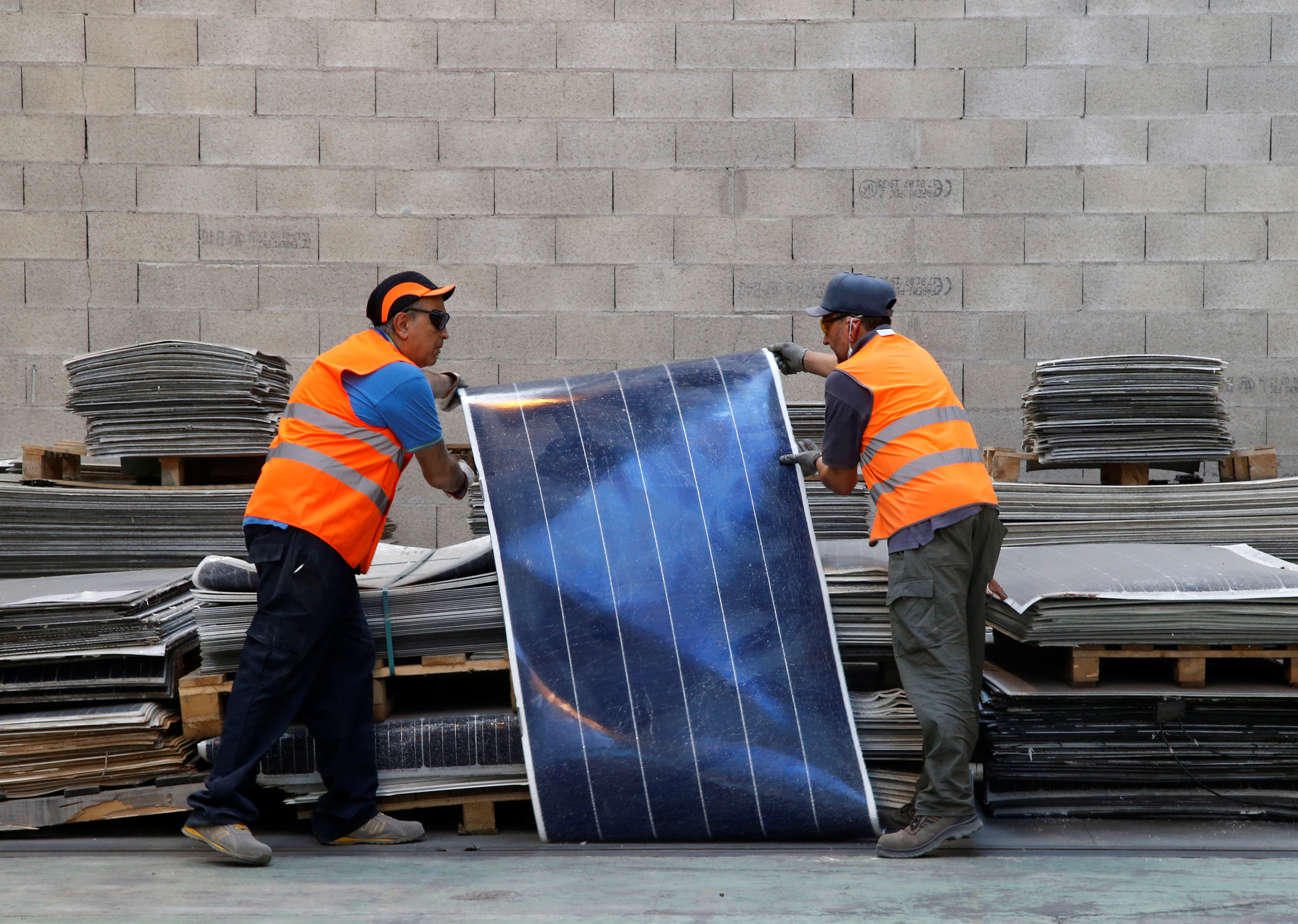Employees work at Veolia's solar panel recycling plant in Rousset, France, June 25, 2018.  At the plant, photovoltaic panels are dissembled and their constituent parts such as glass, aluminium, silicon and plastics are recycled.  REUTERS/Jean-Paul Pelissier - RC137C601D50