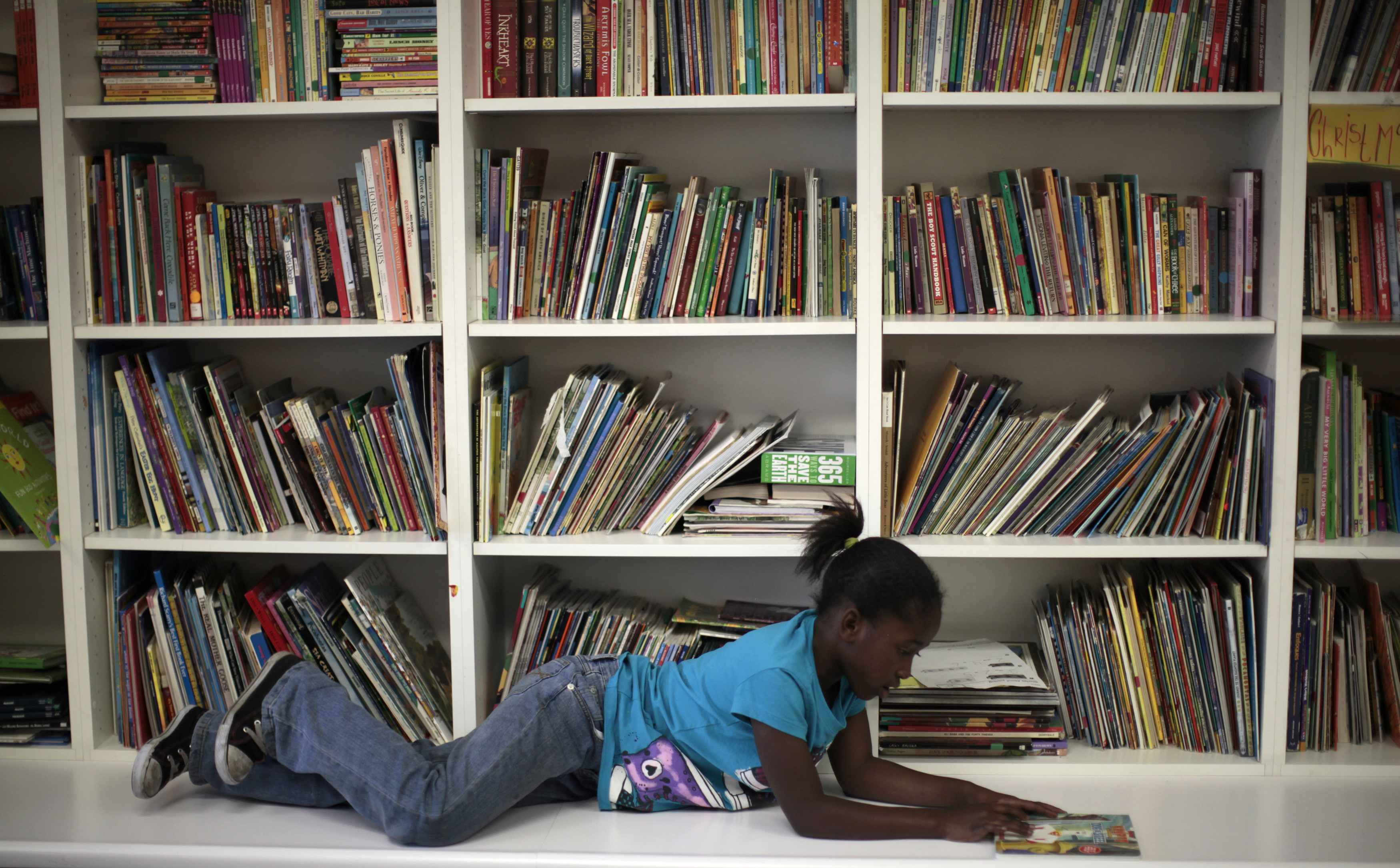 Iana Williams, 8, who is homeless, reads a book at a School on Wheels' after-school program in Los Angeles, February 9, 2012. School on Wheels provides tutoring and educational mentoring to homeless children. A recent report by the National Alliance to End Homelessness found that California's population of homeless families increased by five percent between 2009 and 2011. It is estimated that there are over 300,000 homeless children in California.  REUTERS/Lucy Nicholson (UNITED STATES - Tags: EDUCATION SOCIETY) - RTR2XKVW