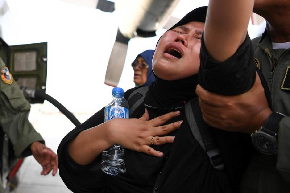 A woman cries as she waits to be evacuated by military aircraft following an earthquake and tsunami at Mutiara Sis Al Jufri Airport in Palu, Central Sulawesi, Indonesia September 30, 2018 in this photo taken by Antara Foto