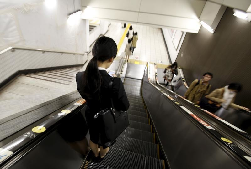 A student job seeker rides on an escalator inside a train station at a business district in Tokyo, Japan, March 31, 2016.