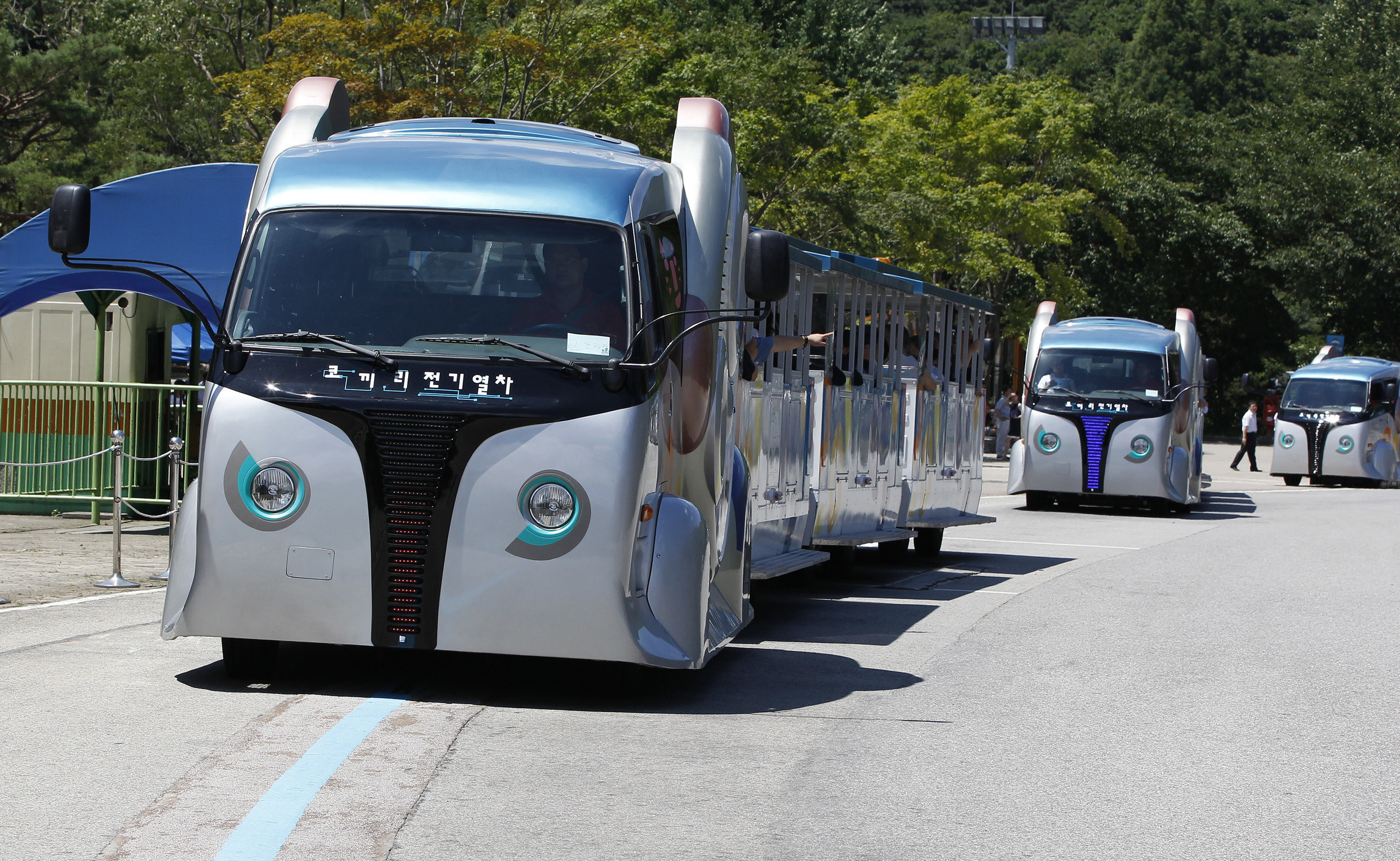 Wireless electric trams move on a road embedded with a power strip after their launch ceremony at Seoul Grand Park in Gwacheon, south of Seoul, July 19, 2011. The Seoul Metropolitan Government and the Korea Advanced Institute of Science and Technology (KAIST) manufactured the tram using a new technology called the On-Line Electric Vehicle (OLEV) system which is remotely charged via electromagnetic fields created by electric cables buried beneath the road. Seoul Grand Park started to run three new wireless electric trams which consume no fossil fuels and do not require any overhead wires or cables. They replaced old diesel-powered carts, local media reported on Tuesday.