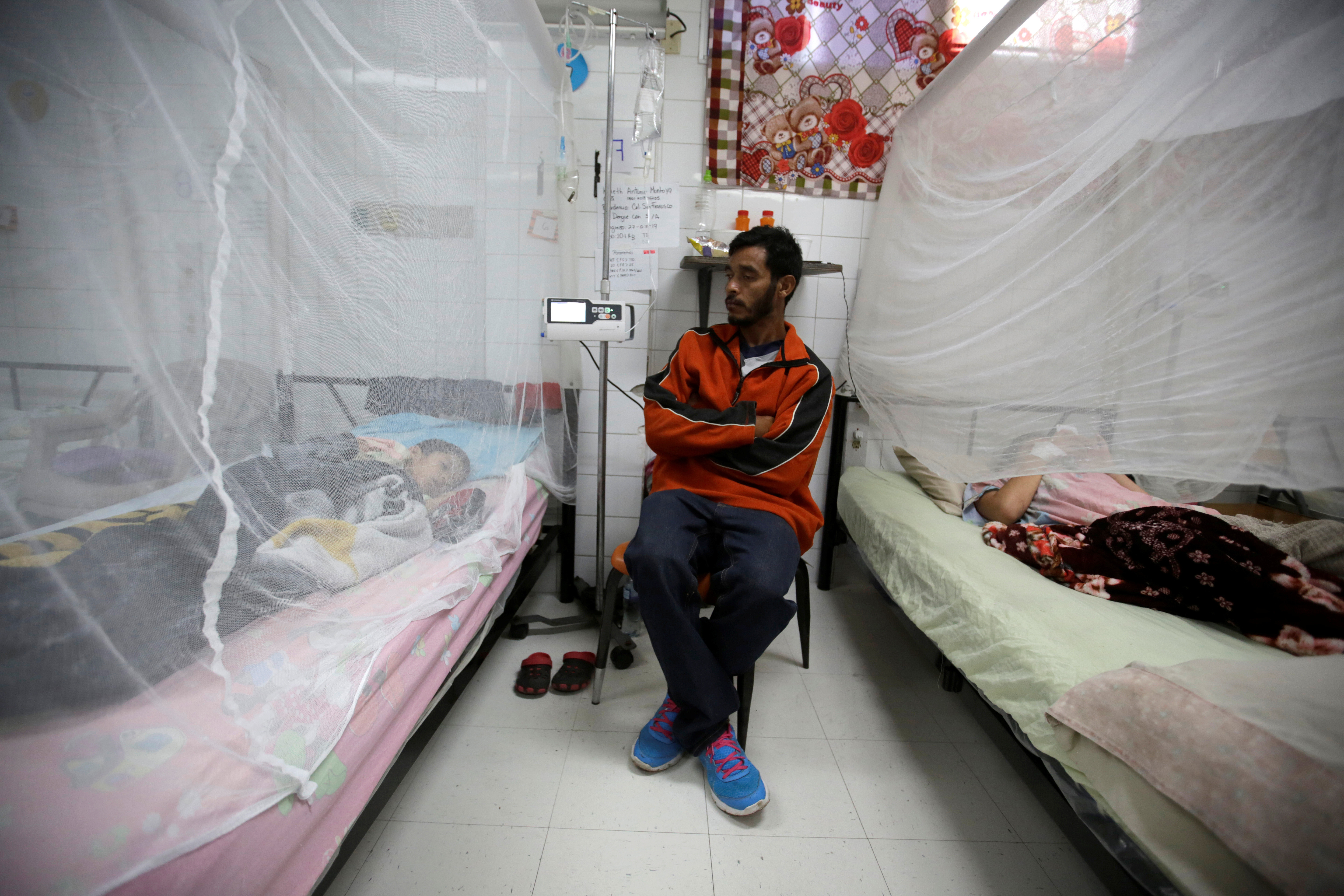 A man sits next to his son as he receives attention for dengue fever at Hospital Escuela in Tegucigalpa, Honduras, July 29, 2019. REUTERS/Jorge Cabrera - RC139FC5F930