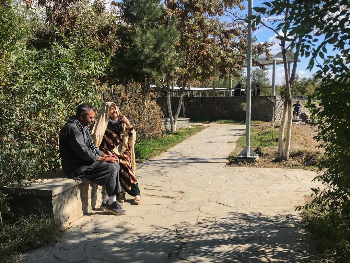 A woman and a man sit on a bench in a park that is being upgraded with wider footpaths, more lights and seating areas as part of a programme to make public spaces safer and more accessible for women in Kabul, Afghanistan. November 6, 2019.