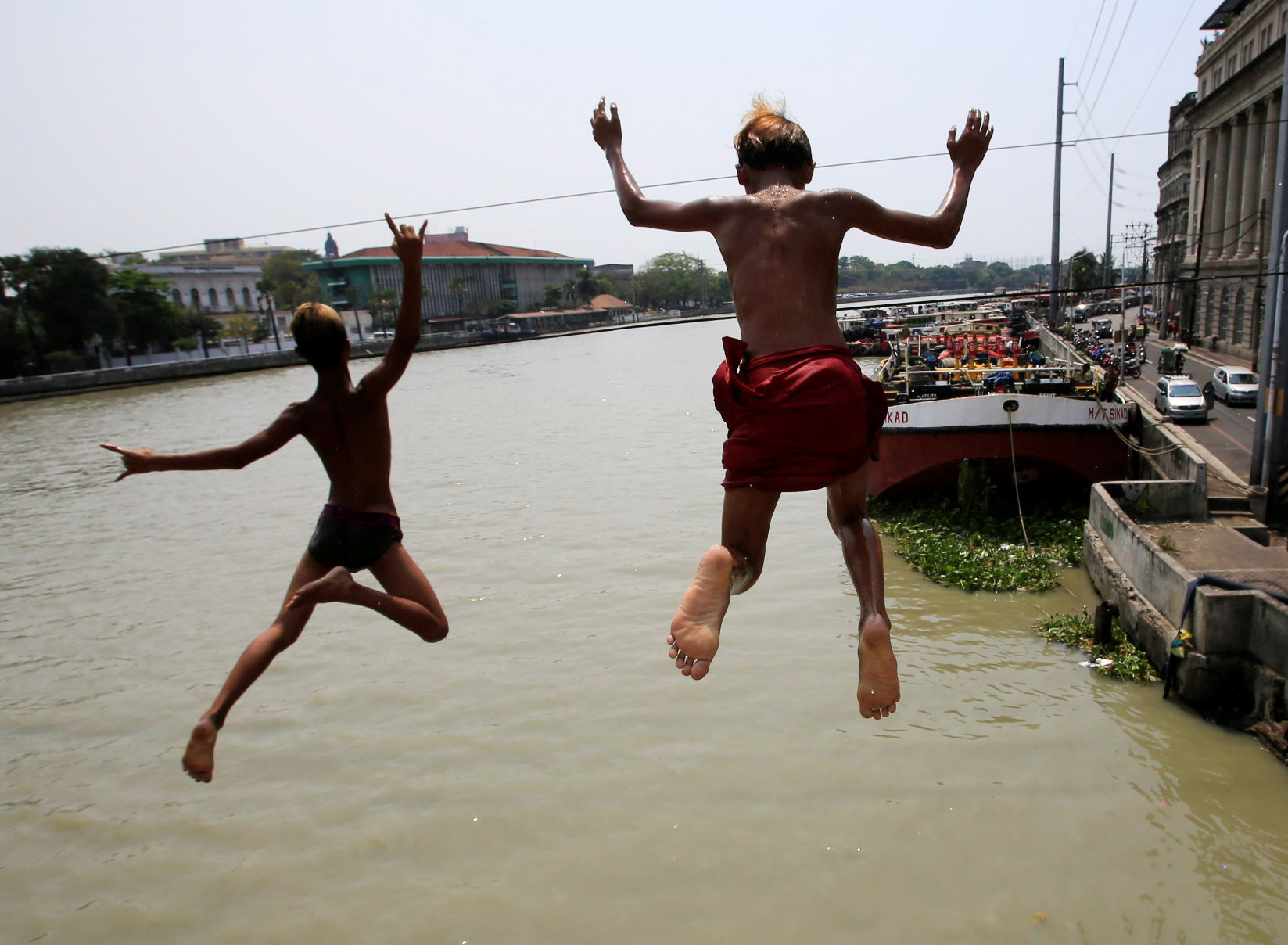 Teenagers jump into the polluted water of Manila Bay, Philippines.